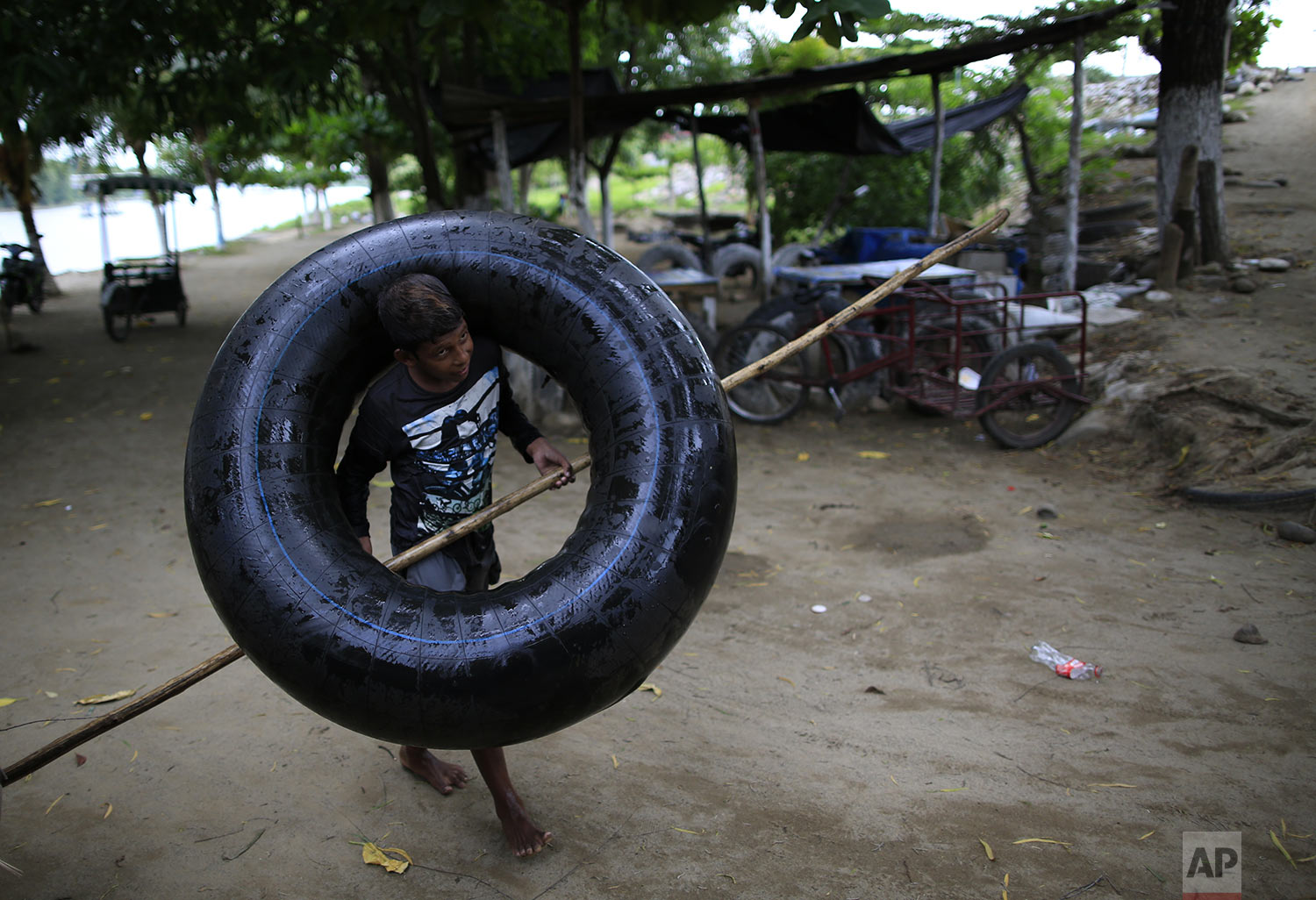 A Mexican boy returns his inner tube and pole to a small business after crossing back across the Suchiate River from Guatemala, in Ciudad Hidalgo, Mexico, June 12, 2019. Mexican officials said Tuesday they were beginning deployment of the country's new National Guard for immigration enforcement, but on Wednesday, commuters, merchandise, and occasional groups of migrants continued to flow freely across the Suchiate on Mexico's porous southern border. (AP Photo/Rebecca Blackwell)