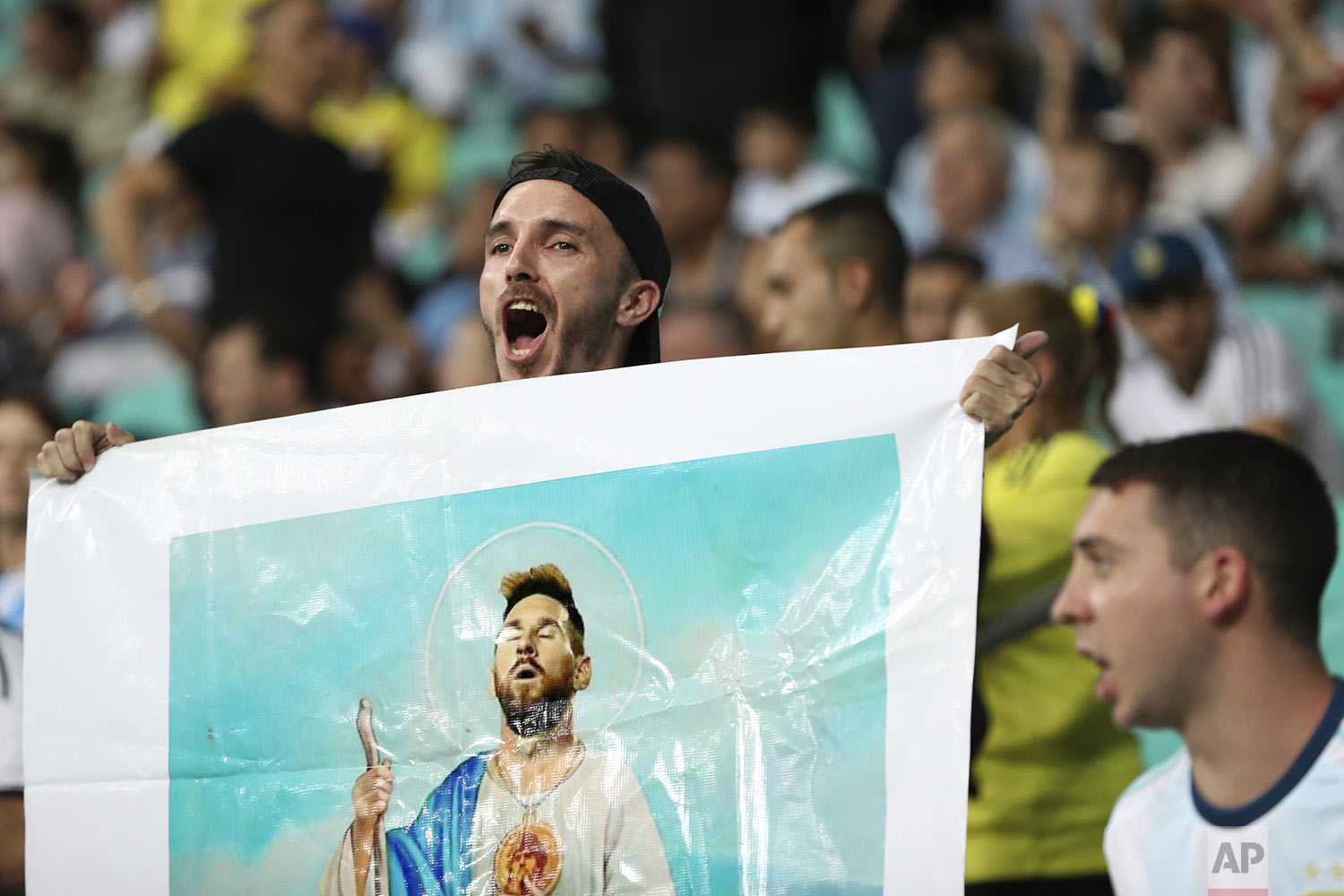 A fan holds an illustration of Argentina's Lionel Messi as a saint during a Copa America Group B soccer match between Argentina and Colombia at the Arena Fonte Nova in Salvador, Brazil, Saturday, June 15, 2019. (AP Photo/Ricardo Mazalan)