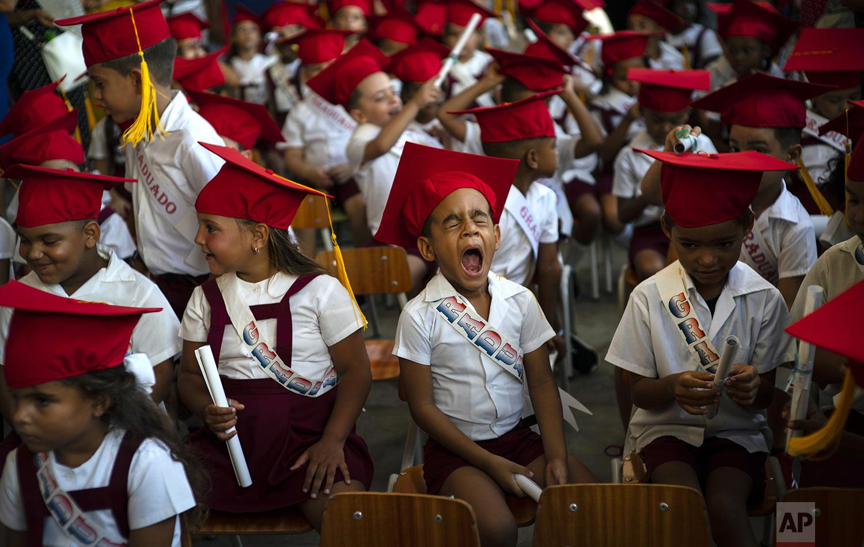 A child yawns during his kindergarten graduation ceremony in Havana, Cuba, Friday, June 21, 2019. (AP Photo/Ramon Espinosa)