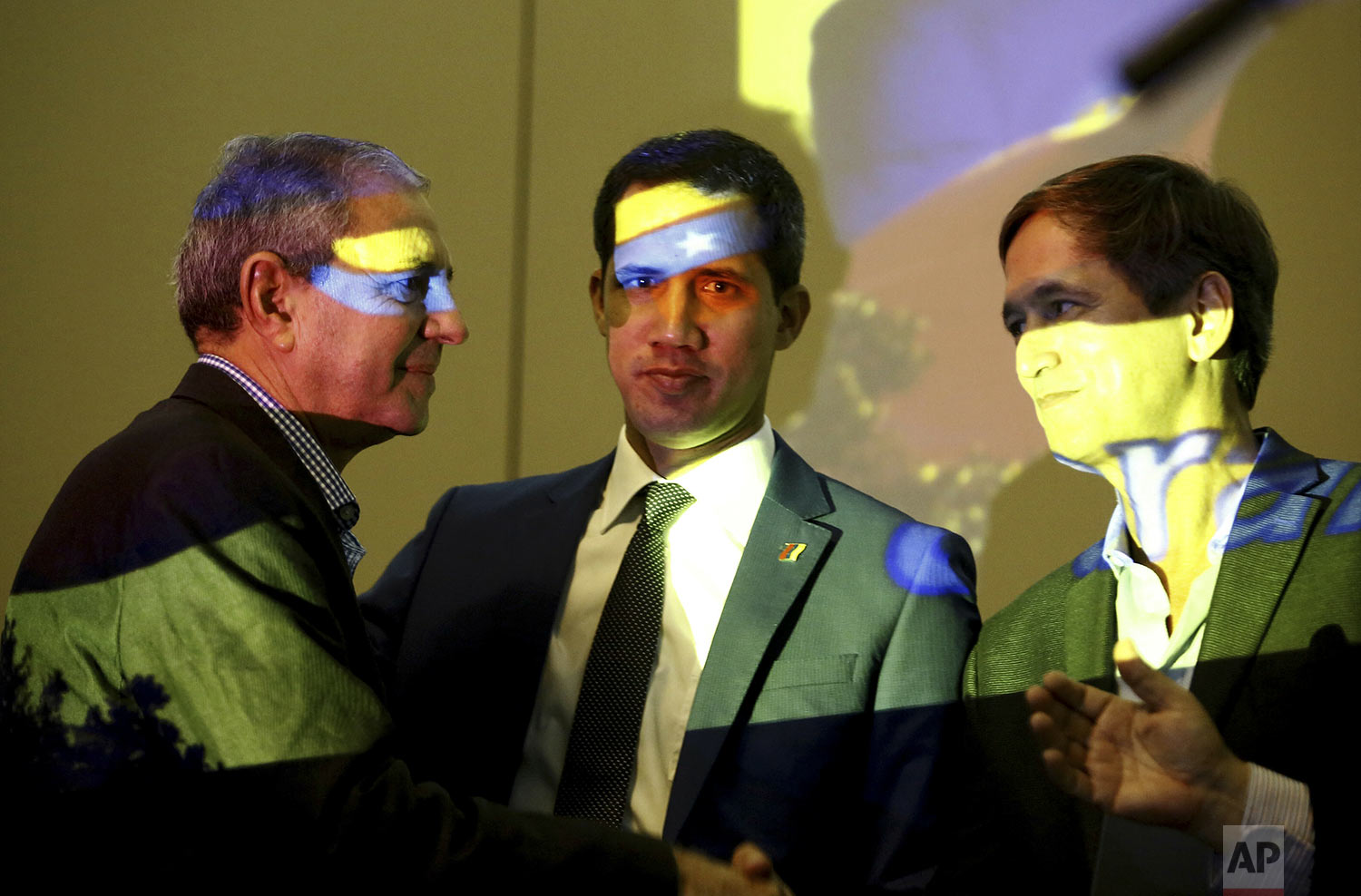 Venezuela's opposition leader and self-proclaimed interim president Juan Guaido, center, speaks with members of the opposition in Carabobo State, Manuel Barreto, left, and Lucio Herrera, prior a speech during a meeting with supporters, at a hotel in Valencia, Venezuela, June 7, 2019. The colors on their faces are the colors of Venezuelan flag projected by a data projector. (AP Photo/Juan Carlos Hernandez)