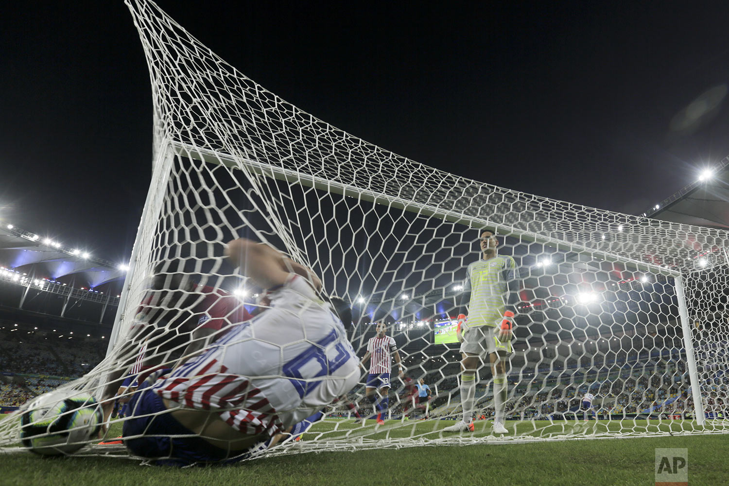 Paraguay's Rodrigo Rojas falls inside his goal after Qatar's Boualem Khoukhi scored his side's second goal during their Copa America Group B soccer match at the Maracana stadium in Rio de Janeiro, Brazil, Sunday, June 16, 2019. (AP Photo/Silvia Izquierdo)