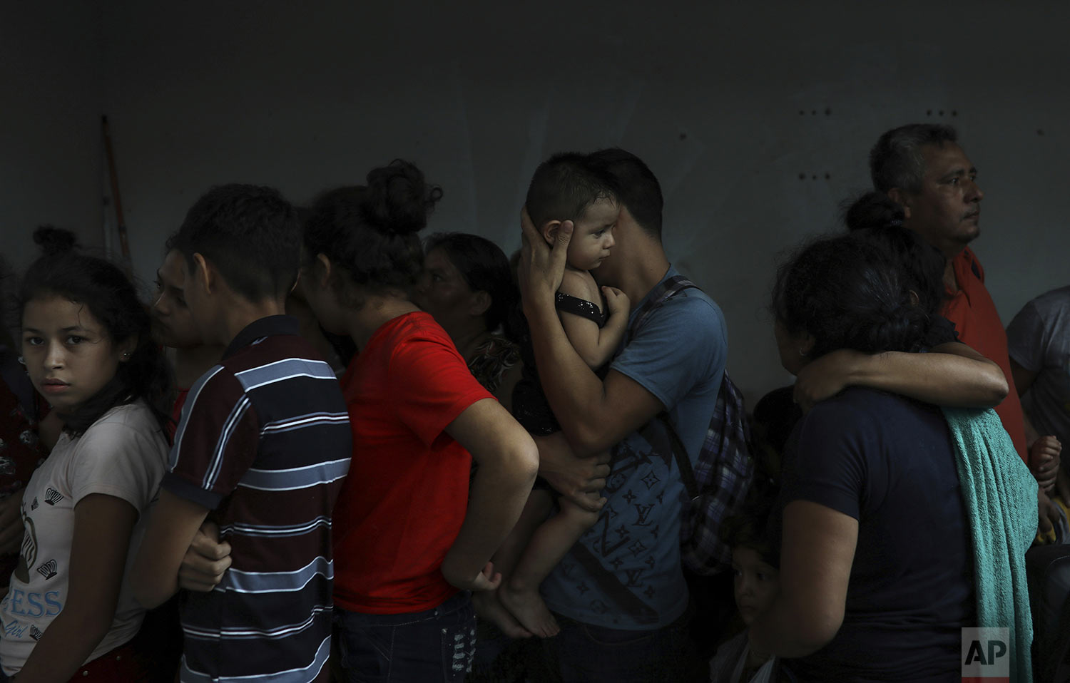 Detained migrants stand together in a storage room at the back of the Azteca Hotel where they tried to hide from  Mexican immigration agents conducting a raid in Veracruz, Mexico, Thursday, June 27, 2019. Under increasing U.S. pressure to reduce the flow of hundreds of thousands of Central Americans through Mexican territory, Mexico's government has stepped up enforcement. (AP Photo/Felix Marquez)