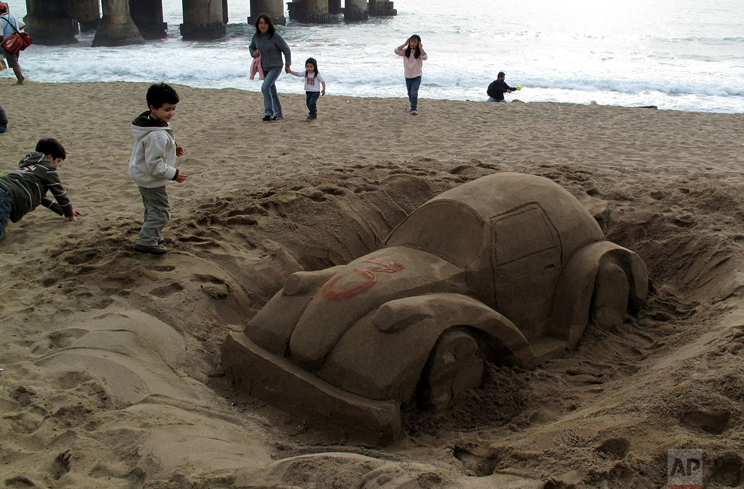 Children play near a sand sculpture in the likeness of a Volkswagen bug on the beach in Vina del Mar, Chile, Aug. 30, 2009. (AP Photo/Santiago Llanquin)