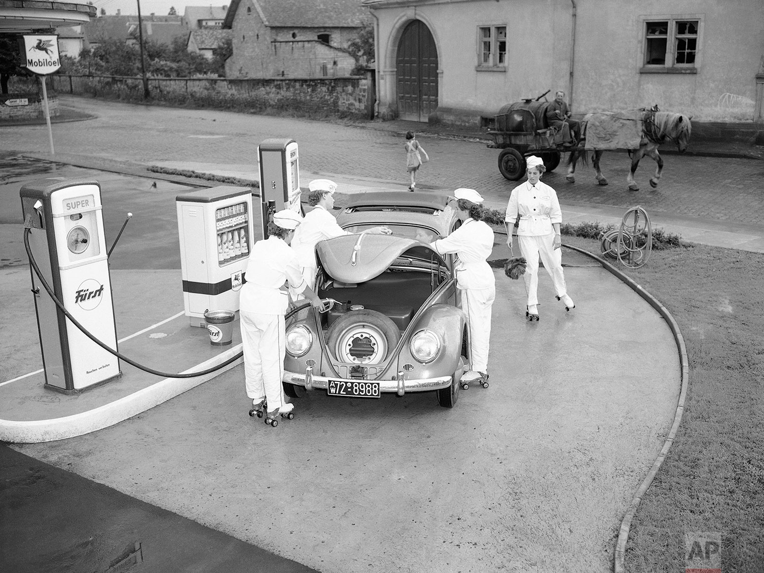 Four female employees tend to a Volkswagen at a gas station in Deidesheim, near Kaiserslautern, Germany, Aug. 23, 1954. (AP Photo/Albert Riethausen)