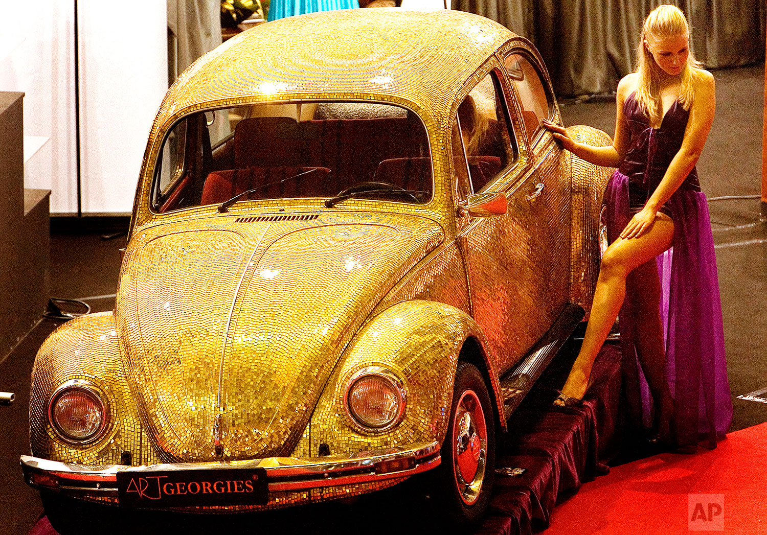 A model poses next to a 1968 Volkswagen Beetle covered in tiles made of a blend of 18 karat gold and glass at the annual Luxury Show in Bucharest, Romania, Dec. 8 2007. (AP Photo/Vadim Ghirda)