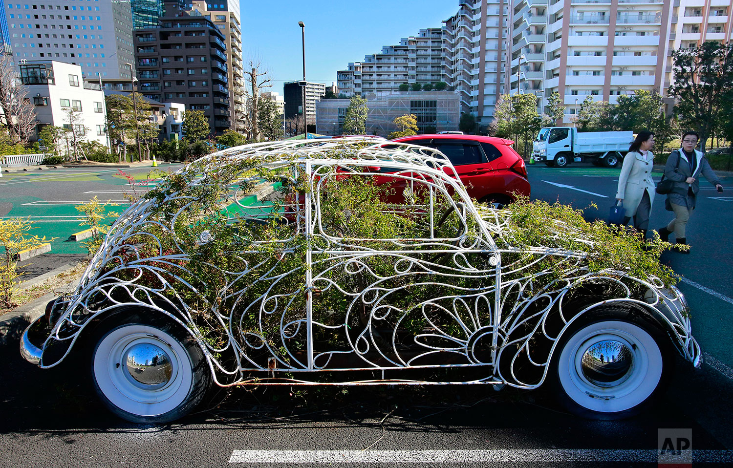 Women walk past the frame of an iconic German Volkswagen Beetle filled with ivy plants used as an outdoor art installation at a parking lot of a shopping mall in Kawasaki, near Tokyo, Jan. 17, 2017. (AP Photo/Shizuo Kambayashi)