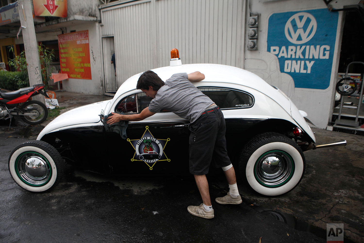 Dany Beltran polishes his 1956 Volkswagen beetle, named the Beltran Volk's Sheriff, outside of his family's Volkswagen repair and service shop in Mexico City, Aug. 7, 2015. (AP Photo/Sofia Jaramillo)