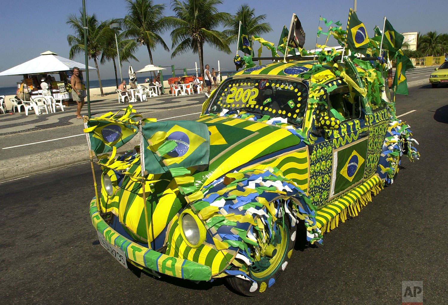 A Volkswagen Beetle, known as Fusca in Brazil, painted in Brazilian colors on the eve of the Brazilian team's next match of the World Cup, drives down Copacabana Beach in Rio de Janeiro, Brazil, June 12, 2002. (AP Photo/Douglas Engle)