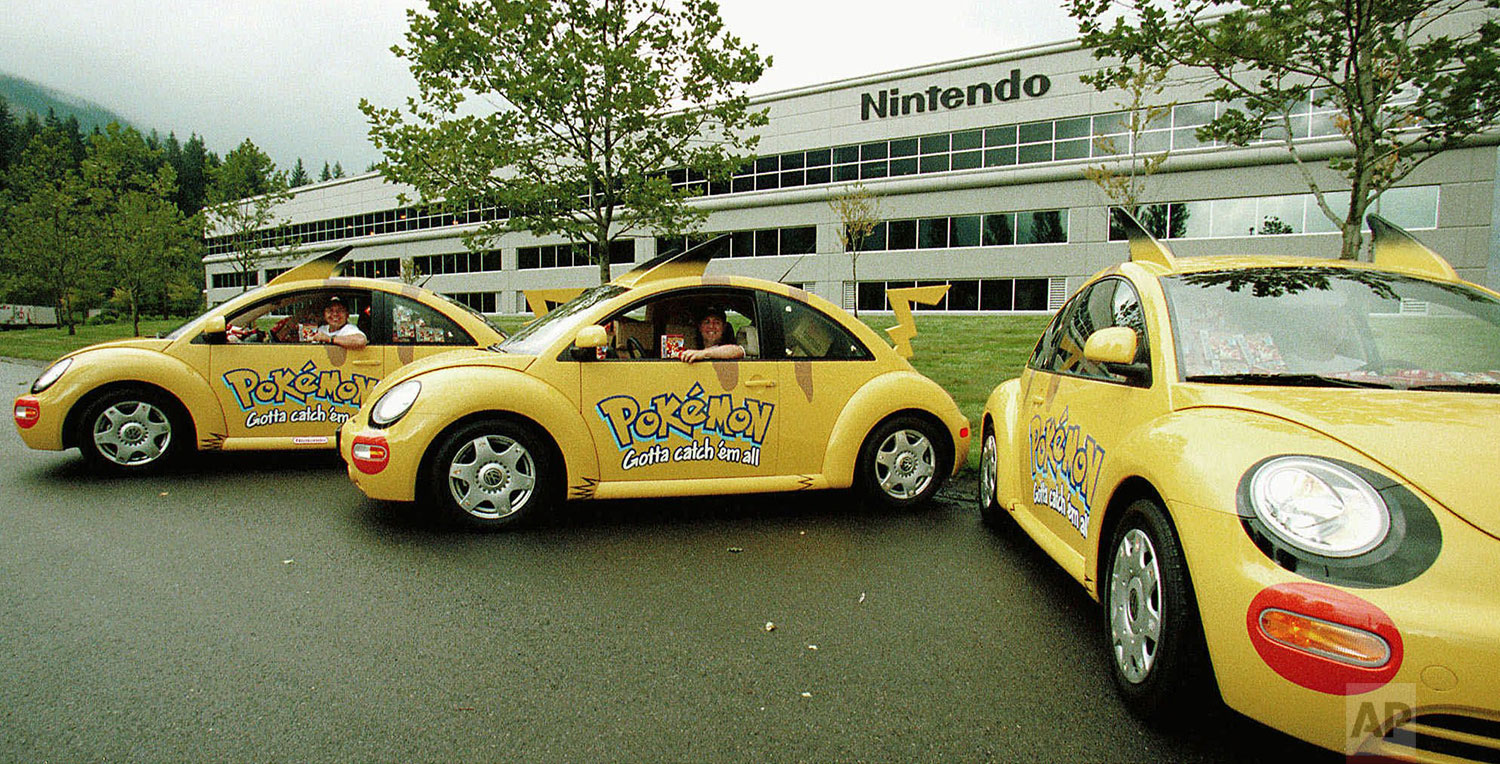 """Pokemon Patrol"" 1998 Volkswagen Beetles park outside Nintendo's North American distribution center in North Bend, Wash., Sept. 25, 1998, with drivers Thom Leonard, left, and Tom Davis. (AP Photo/Joe Brockert)"