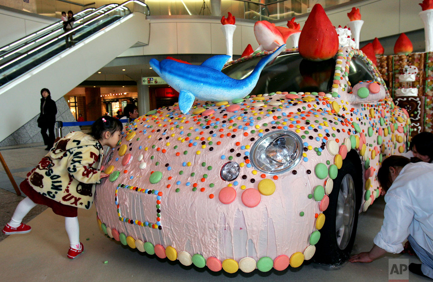A young girl has a little taste of a cookie attached to a Volkswagen Beetle coated with white chocolate flavored with the use of strawberry as it was created by popular chefs and on display at Harumi Triton shopping complex in Tokyo, Jan. 29, 2005 ahead of Valentine's Day.  (AP Photo/Koji Sasahara)