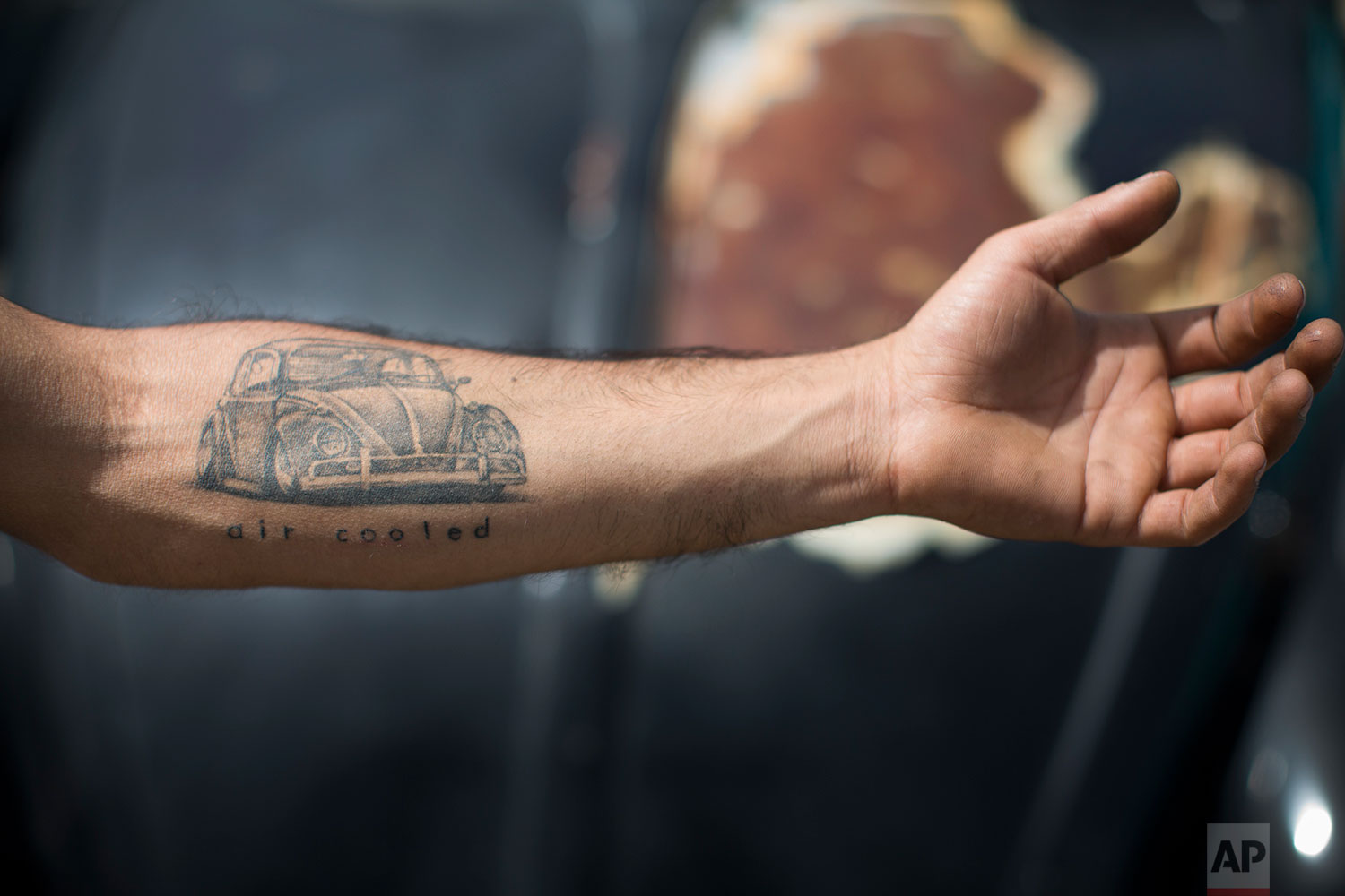 "A Volkswagen Beetle owner shows his tattoo during the annual gathering of the ""Beetle club"" in Yakum, central Israel, April 21, 2017. (AP Photo/Oded Balilty)"
