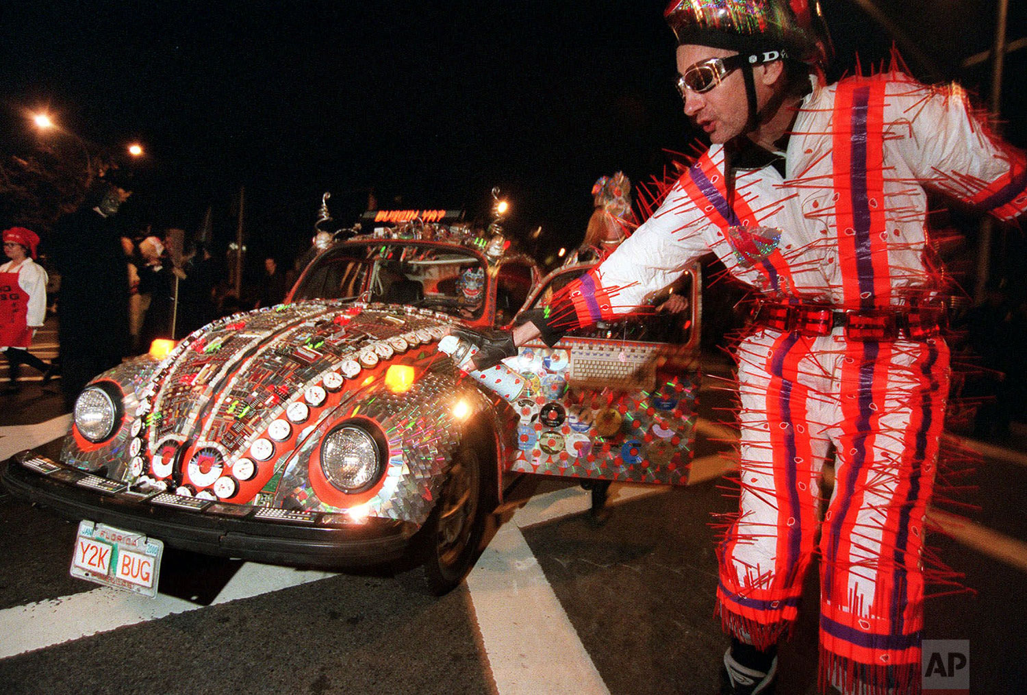 "Dick Darling, of the Manhattan borough of New York, portrays a ""y2k lightning bug"" as he rollerblades in front of a 1974 Volkswagen Beetle named ""Y2K BUG"" during the annual Greenwich Village Halloween parade in New York, Oct. 31, 1999. (AP Photo/Lynsey Addario)"