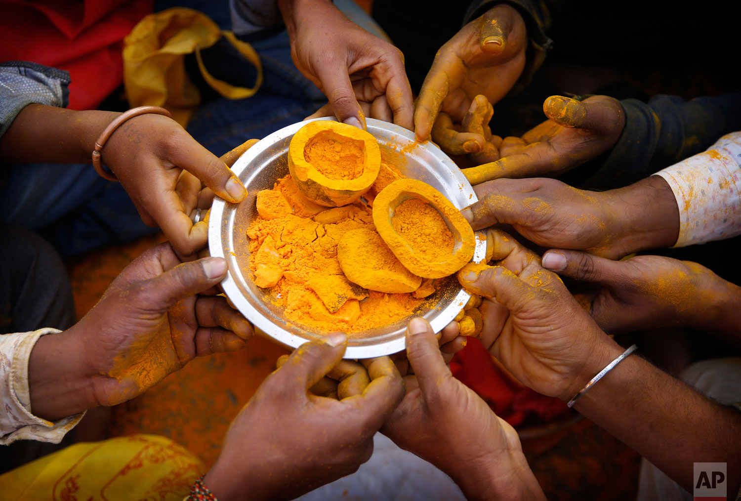 Devotees hold a plate with turmeric as they offer prayers during the celebration of the Bhandara Festival, or the Festival of Turmeric, at the Jejuri temple in Pune district, Maharashtra state, India. During the festival, devotees use the golden powder to worship the deity Lord Khandoba, widely known as a descendant of the sun, and to celebrate his victory over the demons Mani and Malla. (AP Photo/Rafiq Maqbool)
