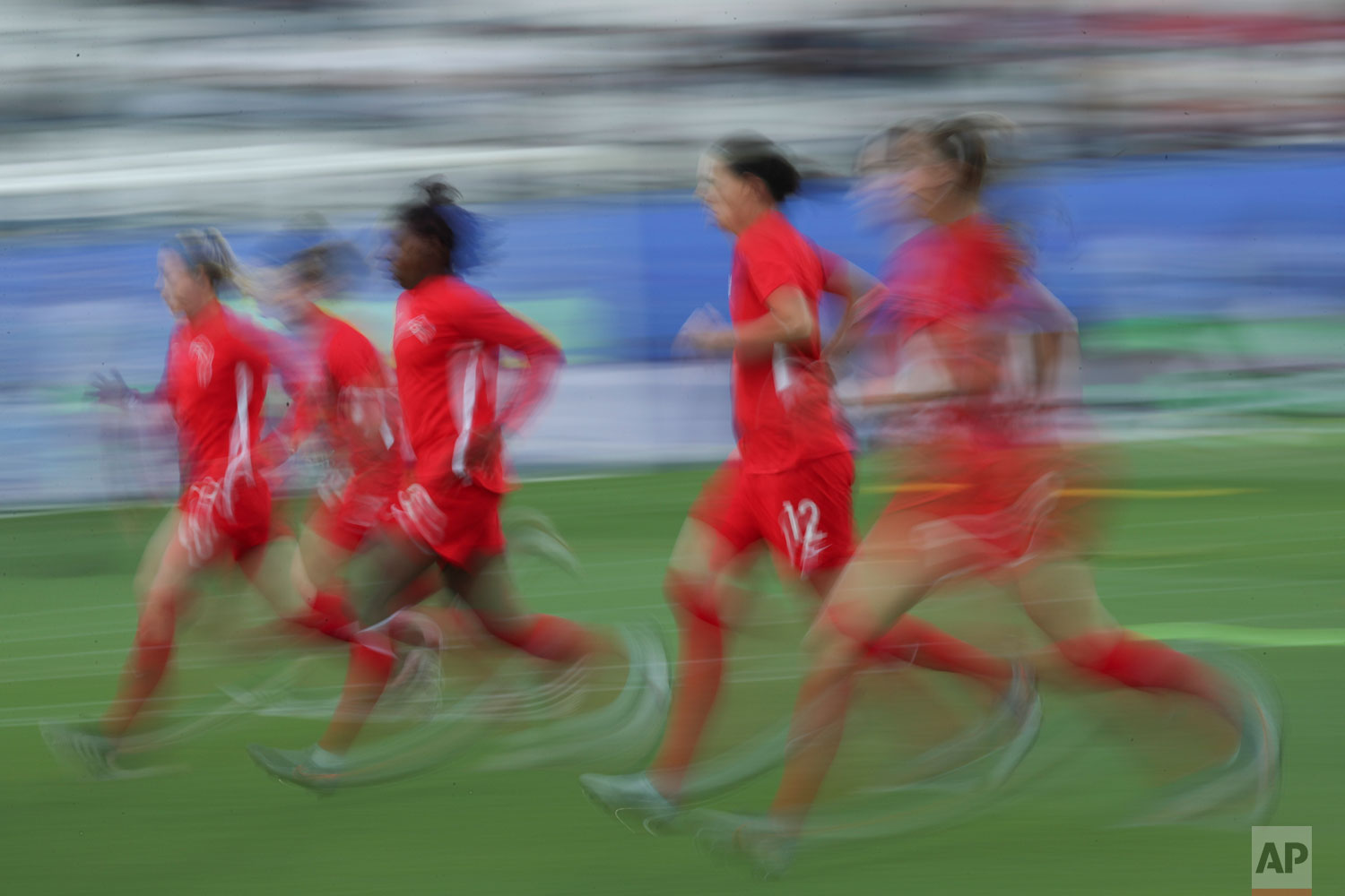 In this image taken with a slow shutter speed Canadian players warm up before the start of the Women's World Cup Group E soccer match between Canada and New Zealand in Grenoble, France, Saturday, June 15, 2019. (AP Photo/Francisco Seco)