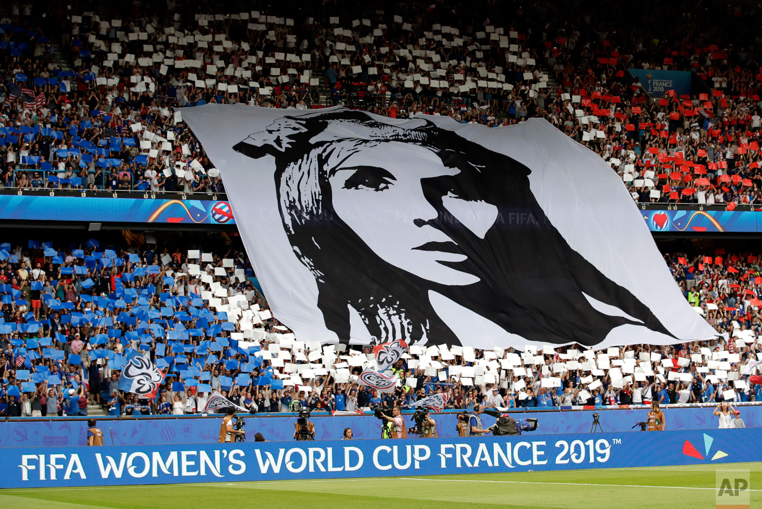 French fans hold a banner that shows Marianne, personification of the French Republic, prior the Women's World Cup quarterfinal soccer match between France and the United States at the Parc des Princes, in Paris, Friday, June 28, 2019.(AP Photo/Alessandra Tarantino)