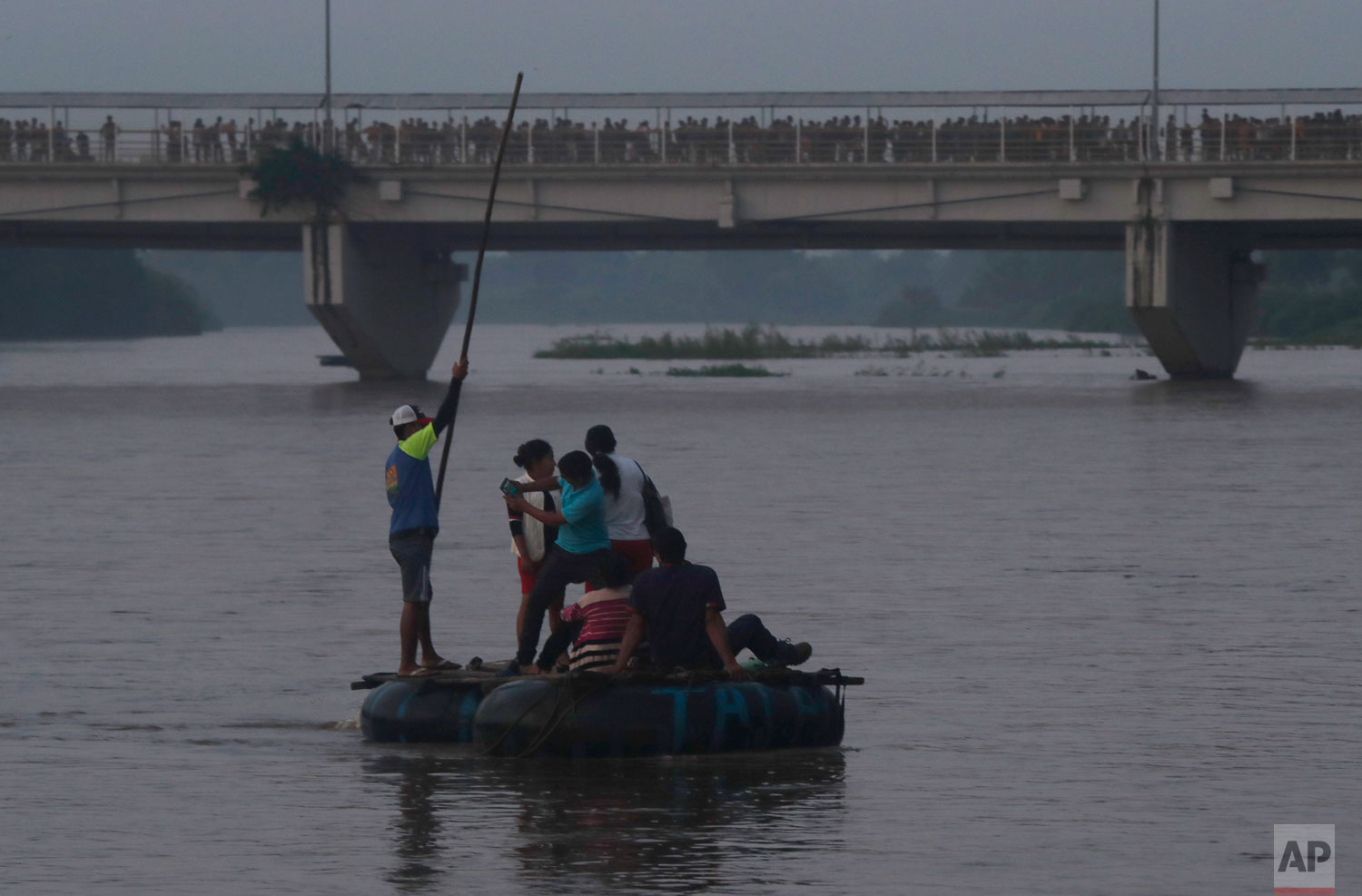 A group of Central American migrants on a raft cross the Suchiate river on the Guatemala – Mexico border as hundreds more walk across the border bridge, near Ciudad Hidalgo, Mexico, Wednesday, June 5, 2019.  (AP Photo/Marco Ugarte)