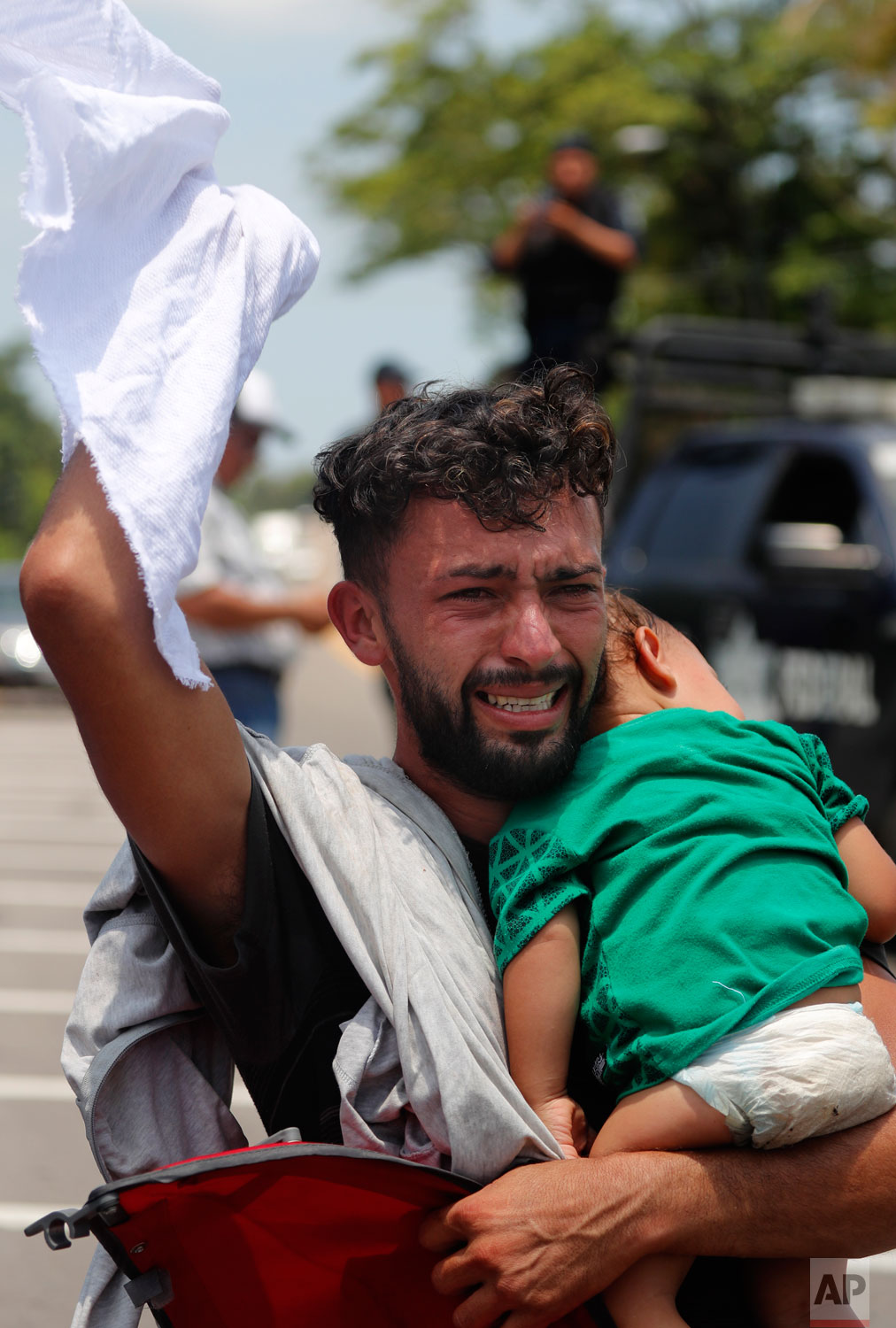 A man begs and prays not to be taken away by Mexican immigration authorities as he holds his child, during a raid on a migrant caravan that had earlier crossed the Mexico - Guatemala border, near Metapa, Chiapas state, Mexico, Wednesday, June 5, 2019. (AP Photo/Marco Ugarte)