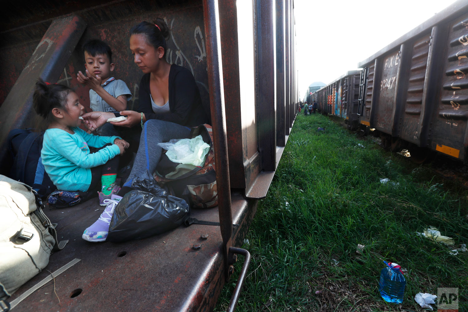 A migrant mother and children ride a freight train on their way north, in Palenque, Chiapas state, Mexico, Monday, June 24, 2019.  (AP Photo/Marco Ugarte)