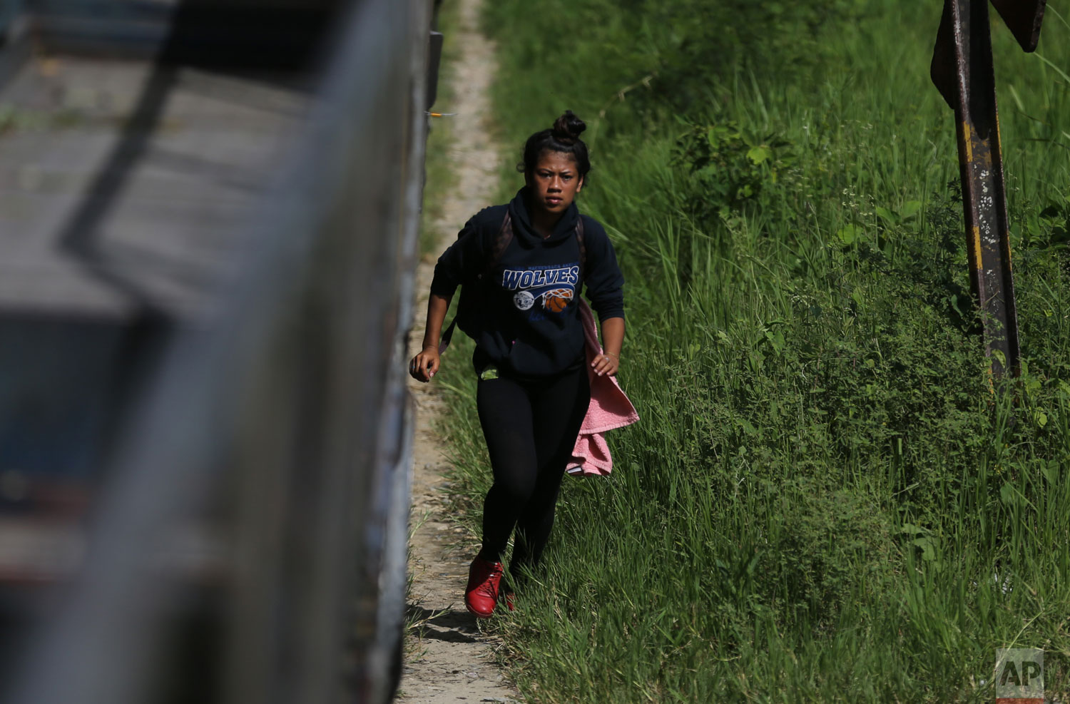 In this June 25, 2019 photo, 19-year-old Honduran Saily Yasm�n Andino runs to climb aboard a freight train, near Salto de Agua, Mexico. Hours later the train stopped near the Tabasco state town of Tacotalpa and Andino hopped off to buy some cheese-stuffed rolls. When the train crowded with migrants began to move again, she hustled to clamber back aboard. But the train suddenly stopped and rolled back. She lost her grip and fell beneath its wheels. (AP Photo/Marco Ugarte)
