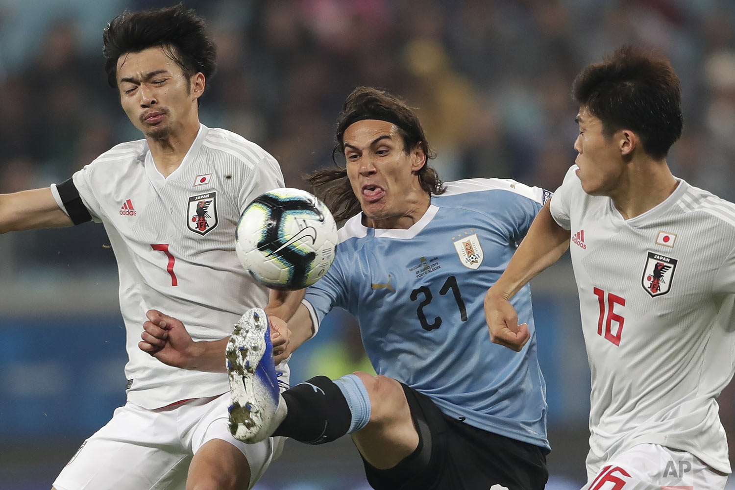 Uruguay's Edinson Cavani vies for the ball between Japan's Takehiro Tomiyasu, right, and  Gaku Shibasaki in Porto Alegre, Brazil, Thursday, June 20, 2019. (AP Photo/Silvia Izquierdo)