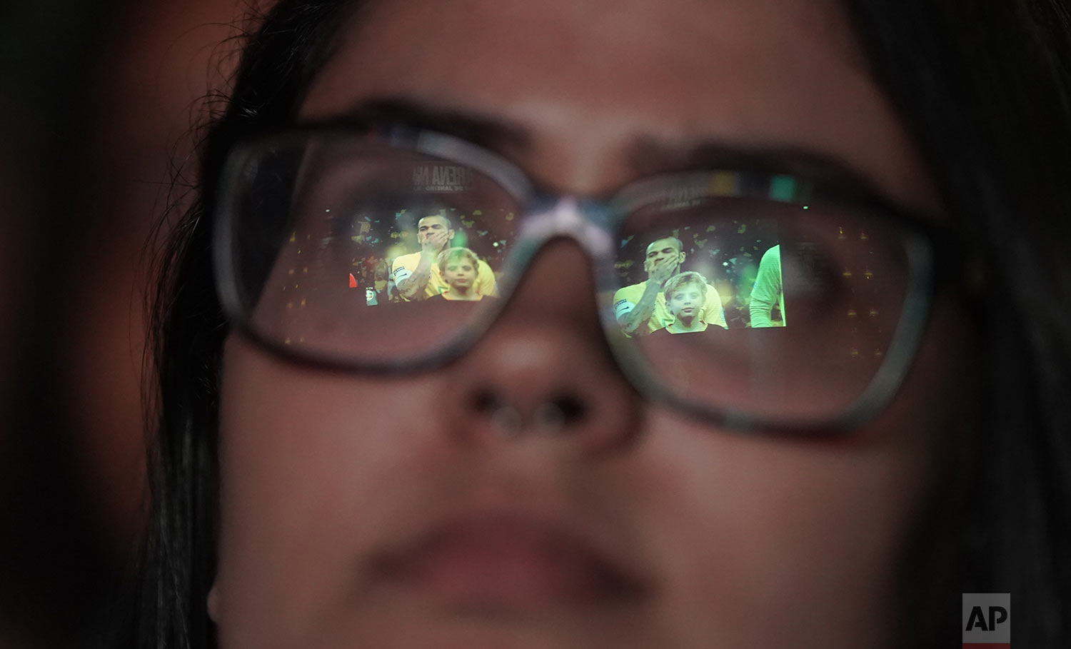 The screen is reflected in a Brazil soccer fan's glasses at the start of an outdoor, live broadcast of a Copa America semifinal soccer match between her team and Argentina in Rio de Janeiro, Brazil, Tuesday, July 2, 2019. (AP Photo/Leo Correa)