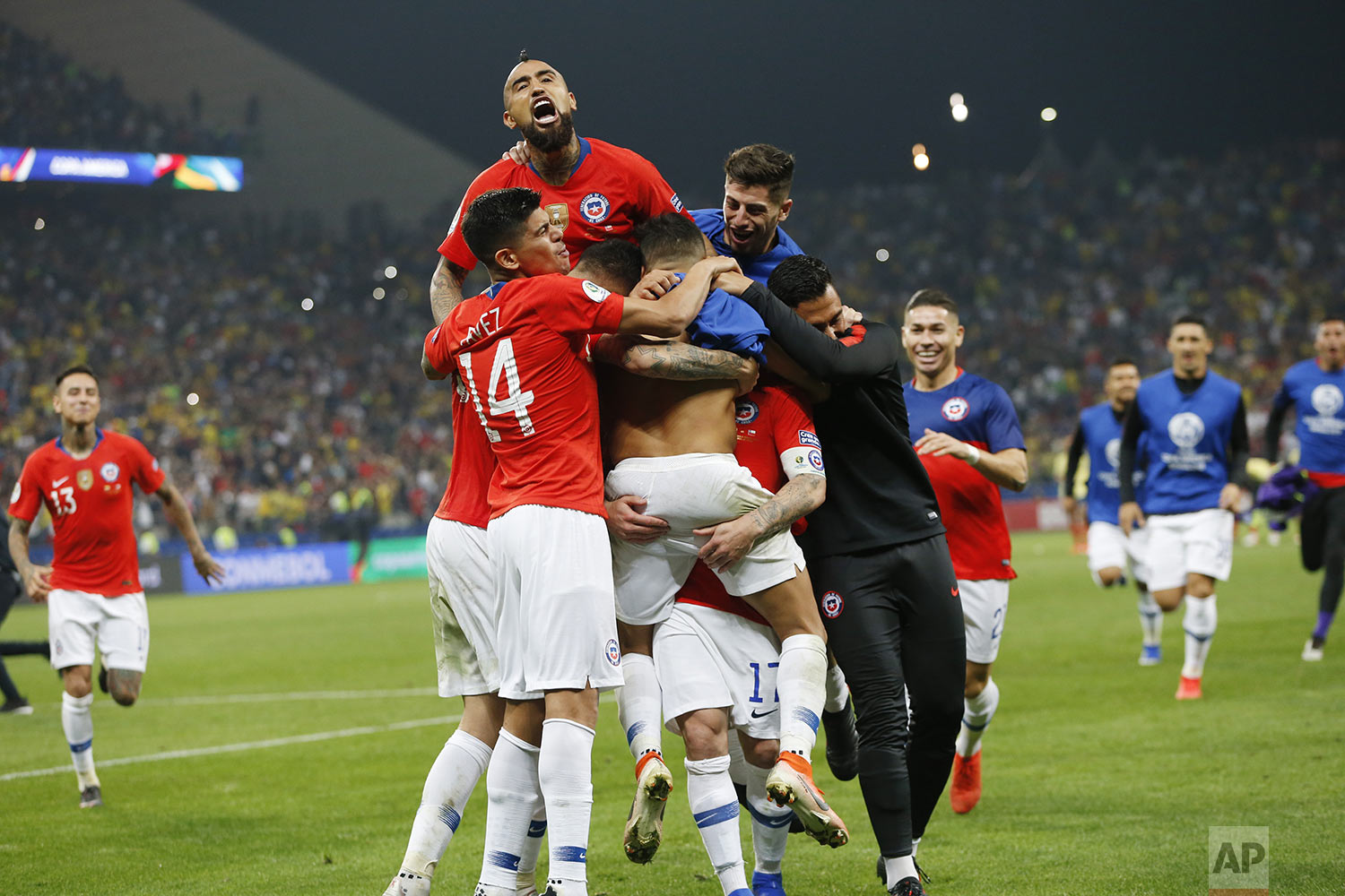 Chile players surround teammate Alexis Sanchez after he scored the winning penalty shot against Colombia during a Copa America quarterfinal soccer match at  Arena Corinthians in Sao Paulo, Brazil, Friday, June 28, 2019. Chile beat Colombia 5-4 on penalties after the match ended 0-0. (AP Photo/Andre Penner)
