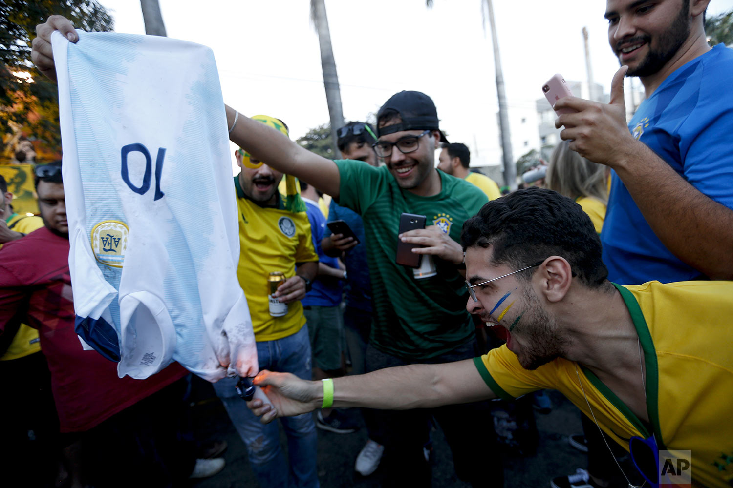 Fans of Brazil light a jersey of Argentina with the number 10, used by Lionel Messi, prior to a Copa America semifinal soccer match between Argentina and Brazil at the Mineirao stadium in Belo Horizonte, Brazil, Tuesday, July 2, 2019. (AP Photo/Natacha Pisarenko)