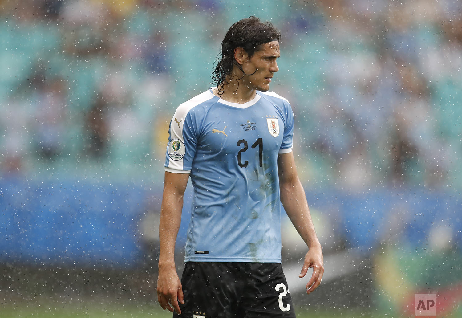 Uruguay's Edinson Cavani stands in the rain  during a Copa America quarterfinal soccer match against Peru at  Arena Fonte Nova in Salvador, Brazil, Saturday, June 29, 2019. (AP Photo/Natacha Pisarenko)