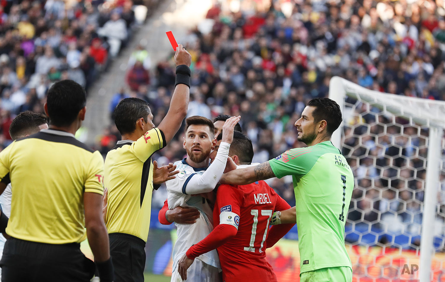 Argentina's Lionel Messi, center left, and Chile's Gary Medel, center right, scuffle as referee Mario Diaz, from Paraguay, shows the red card to both of them during the Copa America third-place soccer match at the Arena Corinthians in Sao Paulo, Brazil, Saturday, July 6, 2019. (AP Photo/Victor R. Caivano)