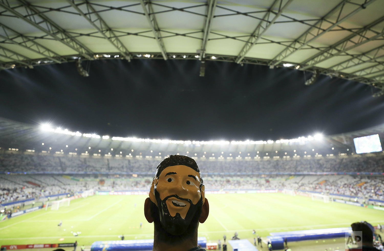 An Argentine fan wears a mask with the image of striker Lionel Messi prior a Copa America Group B soccer match against Paraguay at Mineirao stadium in Belo Horizonte, Brazil, Wednesday, June 19, 2019. (AP Photo/Ricardo Mazalan)
