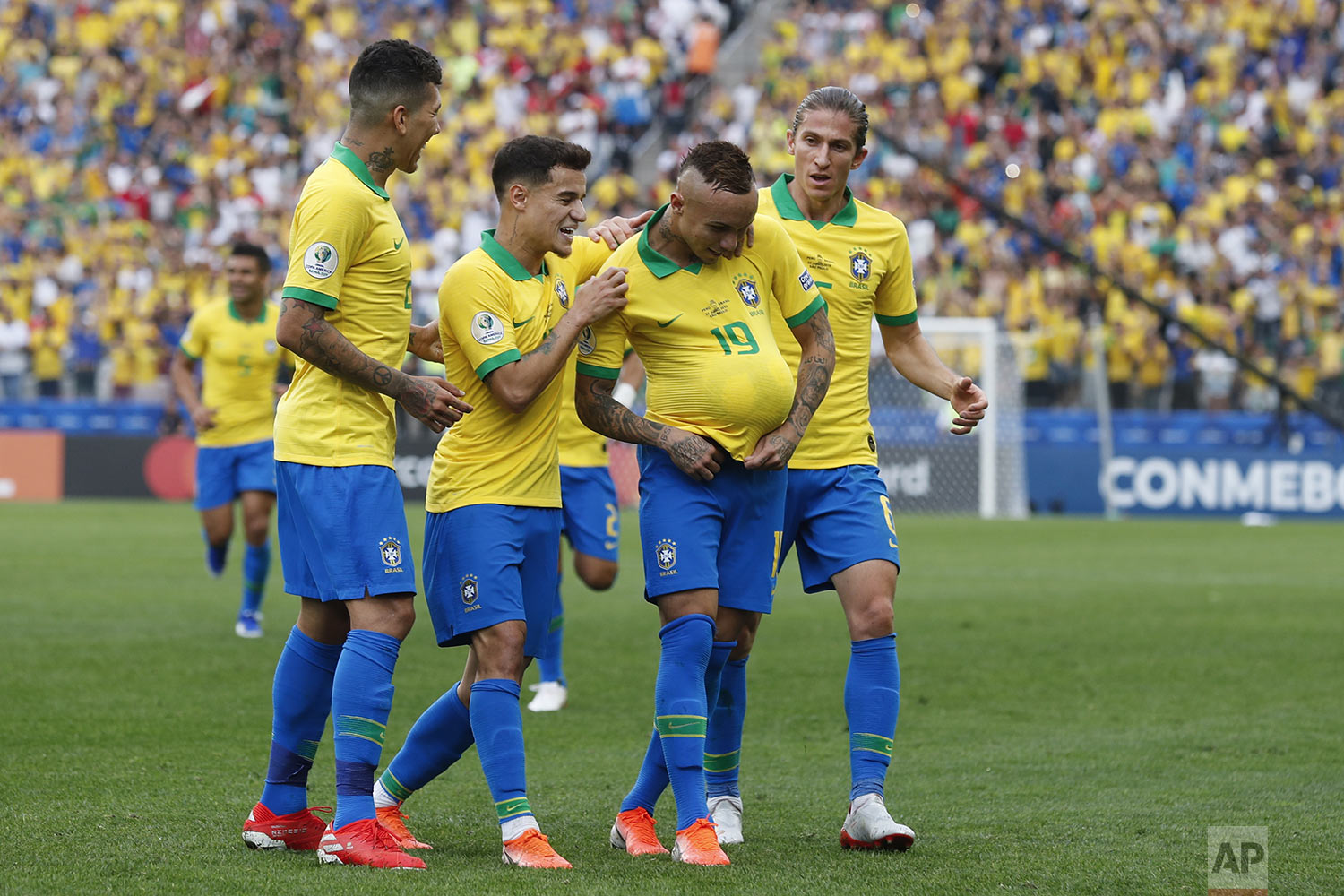 Brazil players congratulate teammate Everton, with the ball under his jersey, after he scored his side's third goal against Peru during a Copa America Group A soccer match at  Arena Corinthians in Sao Paulo, Brazil, Saturday, June 22, 2019. (AP Photo/Victor R. Caivano)