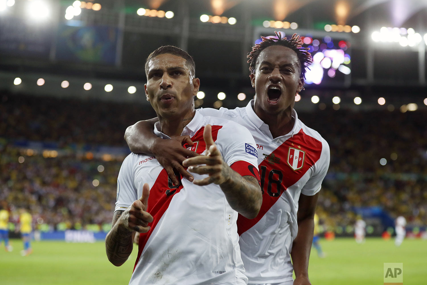 Peru's Paolo Guerrero, left, celebrates with teammate Andre Carrillo, after scoring a penalty kick against Brazil during the final soccer match of the Copa America at Maracana stadium in Rio de Janeiro, Brazil, Sunday, July 7, 2019. (AP Photo/Victor R. Caivano)