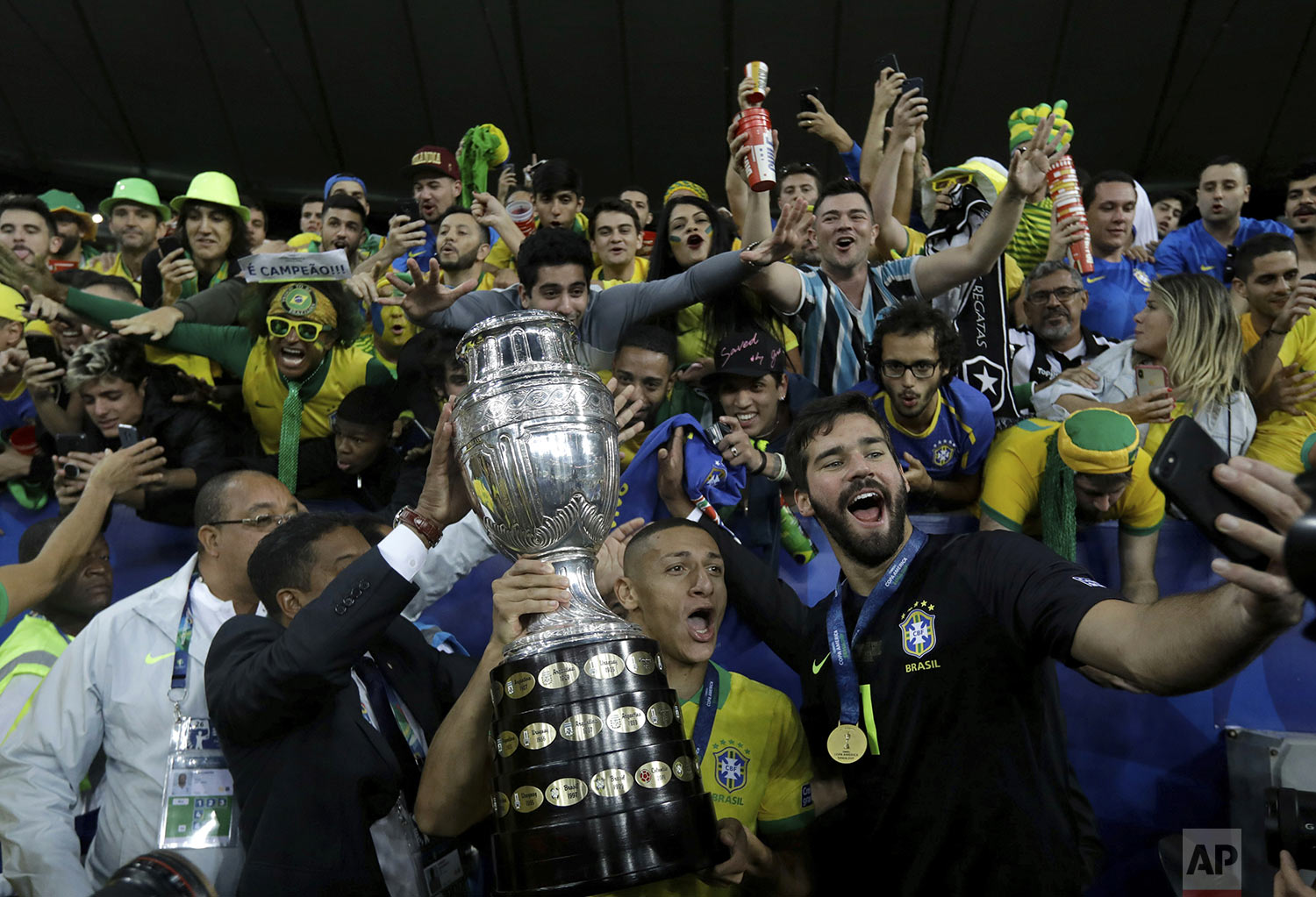 Brazil's Richarlison holds the Copa America trophy as goalkeeper Alisson takes their selfie with fans after winning the final Copa America soccer match against Peru at Maracana stadium in Rio de Janeiro, Brazil, Sunday, July 7, 2019. Brazil won 3-1. (AP Photo/Leo Correa)