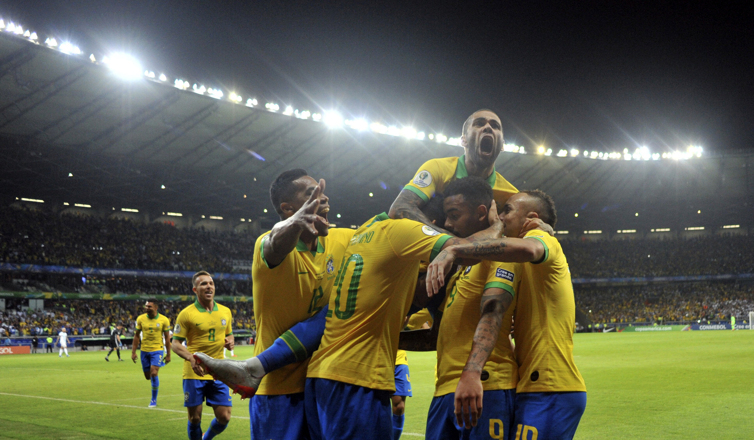 Brazil's Dani Alves, top, jumps on top of his teammates after teammate Gabriel Jesus scored their team's first goal against Argentina during a Copa America semifinal soccer match at Mineirao stadium in Belo Horizonte, Brazil, Tuesday, July 2, 2019. (AP Photo/Eugenio Savio)
