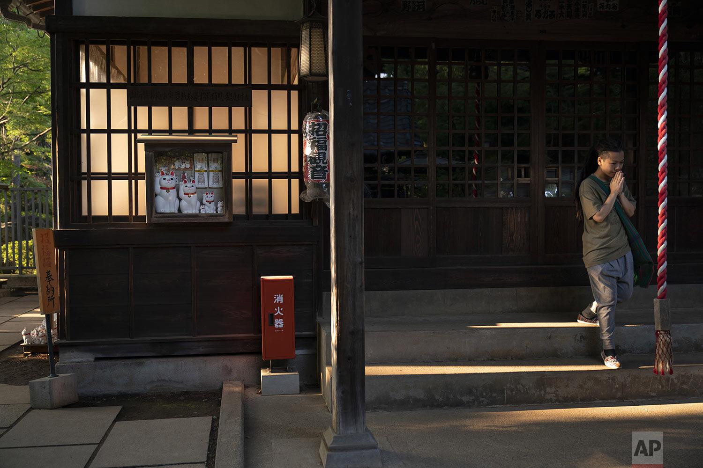 A tourist visiting from Hong Kong prays at Gotokuji Temple in Tokyo, Tuesday, June 25, 2019. (AP Photo/Jae C. Hong)
