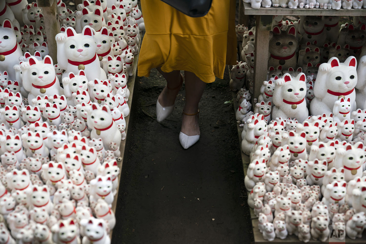 A tourist walk between beckoning cat figurines after posing for photos with them at Gotokuji Temple in Tokyo, Tuesday, June 25, 2019. (AP Photo/Jae C. Hong)