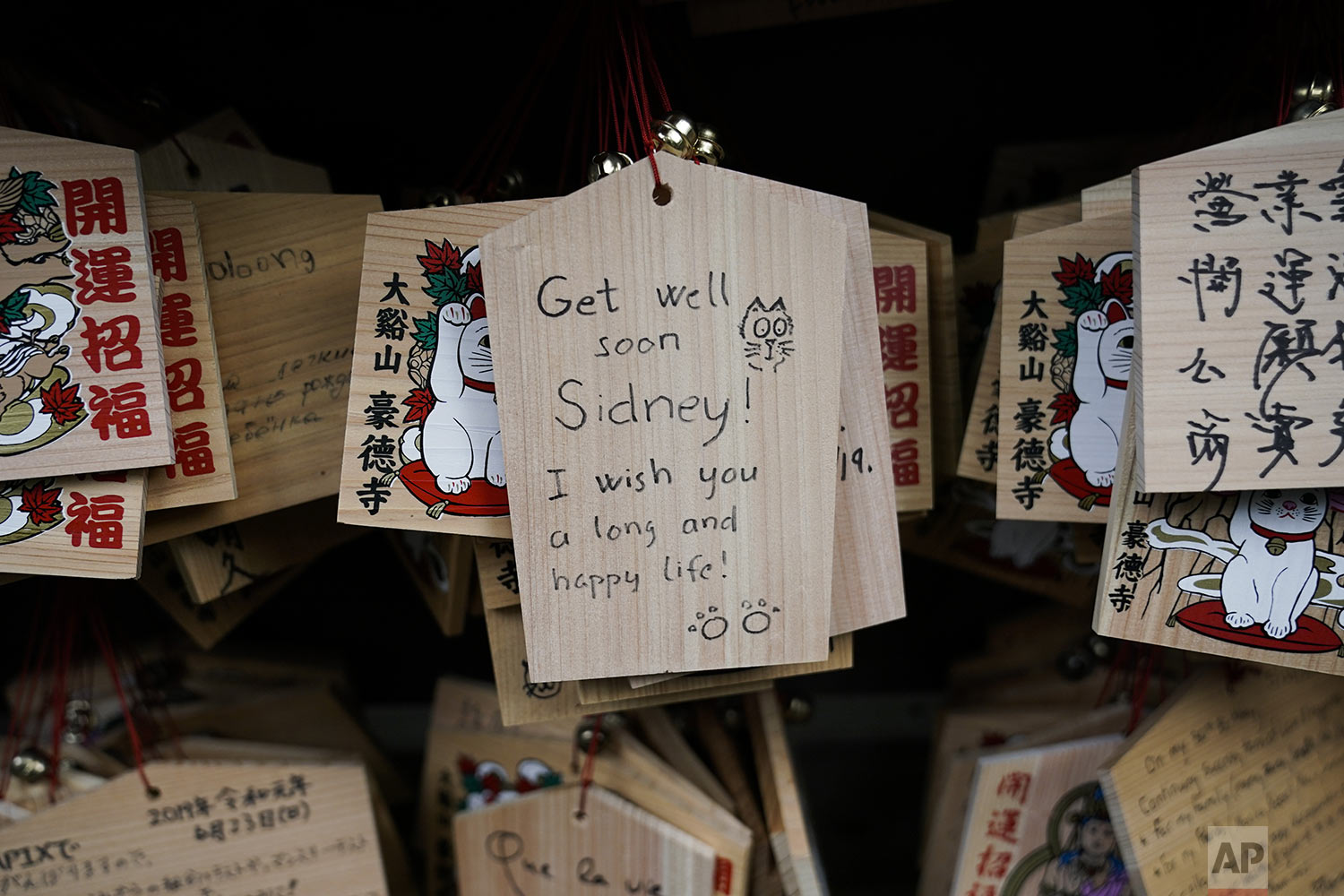 A prayer is written on a wooden panel donned with an image of a beckoning cat at Gotokuji Temple in Tokyo, Tuesday, July 2, 2019. (AP Photo/Jae C. Hong)