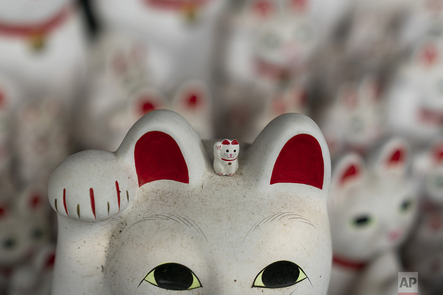 A small beckoning cat figurine is placed on top of a large statue at Gotokuji Temple in Tokyo, Tuesday, June 25, 2019. (AP Photo/Jae C. Hong)