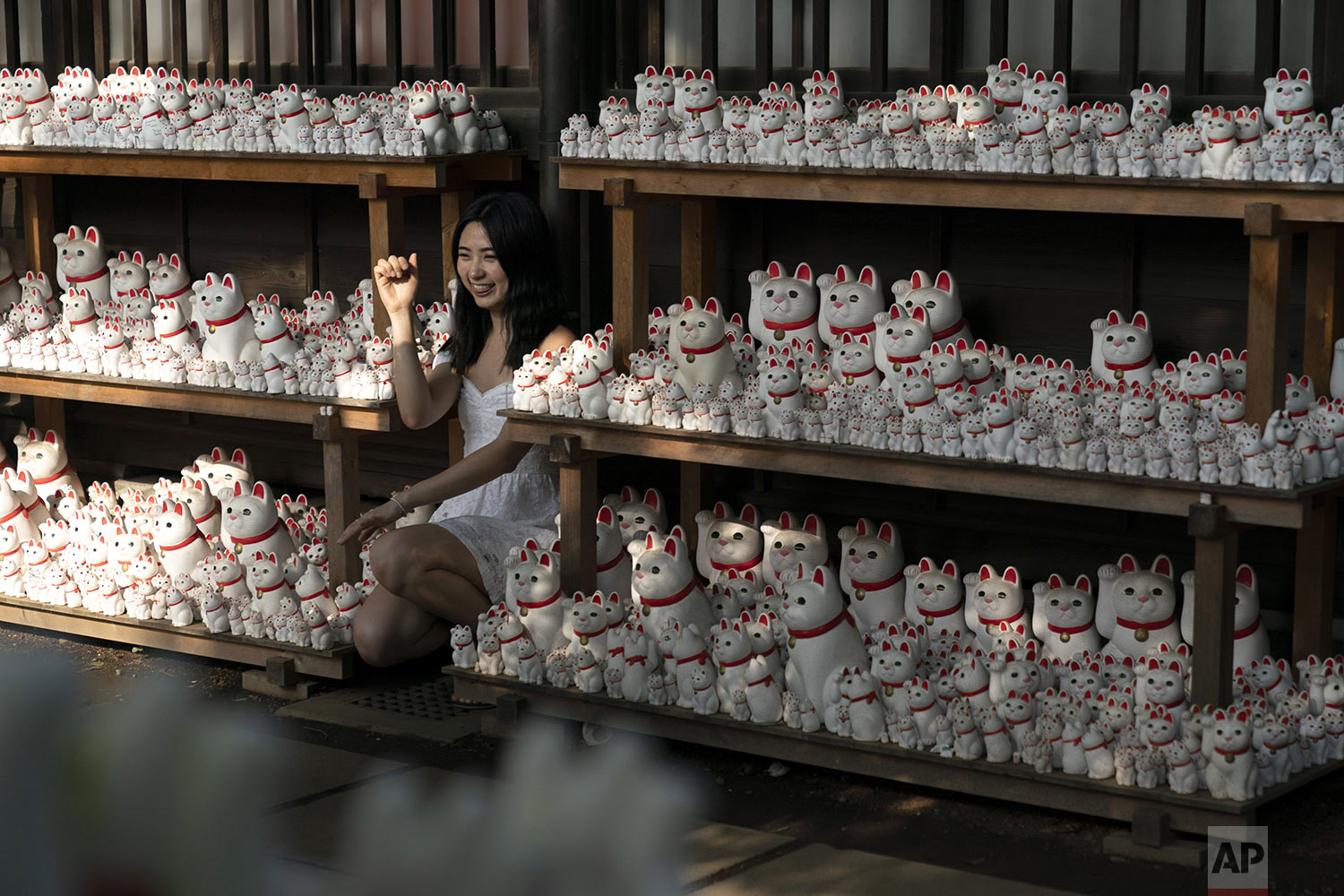 A woman poses for photos with beckoning cat figurines at Gotokuji Temple in Tokyo, Tuesday, June 25, 2019. (AP Photo/Jae C. Hong)