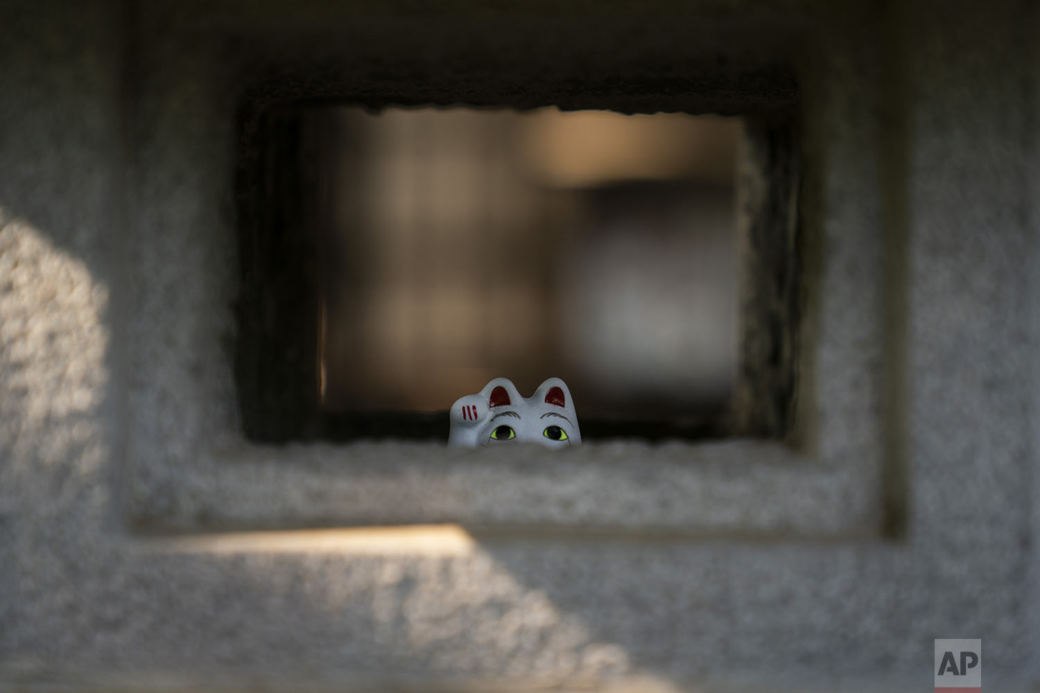 A small beckoning cat figurine is placed inside a stone lamp at Gotokuji Temple in Tokyo, Tuesday, June 25, 2019. (AP Photo/Jae C. Hong)
