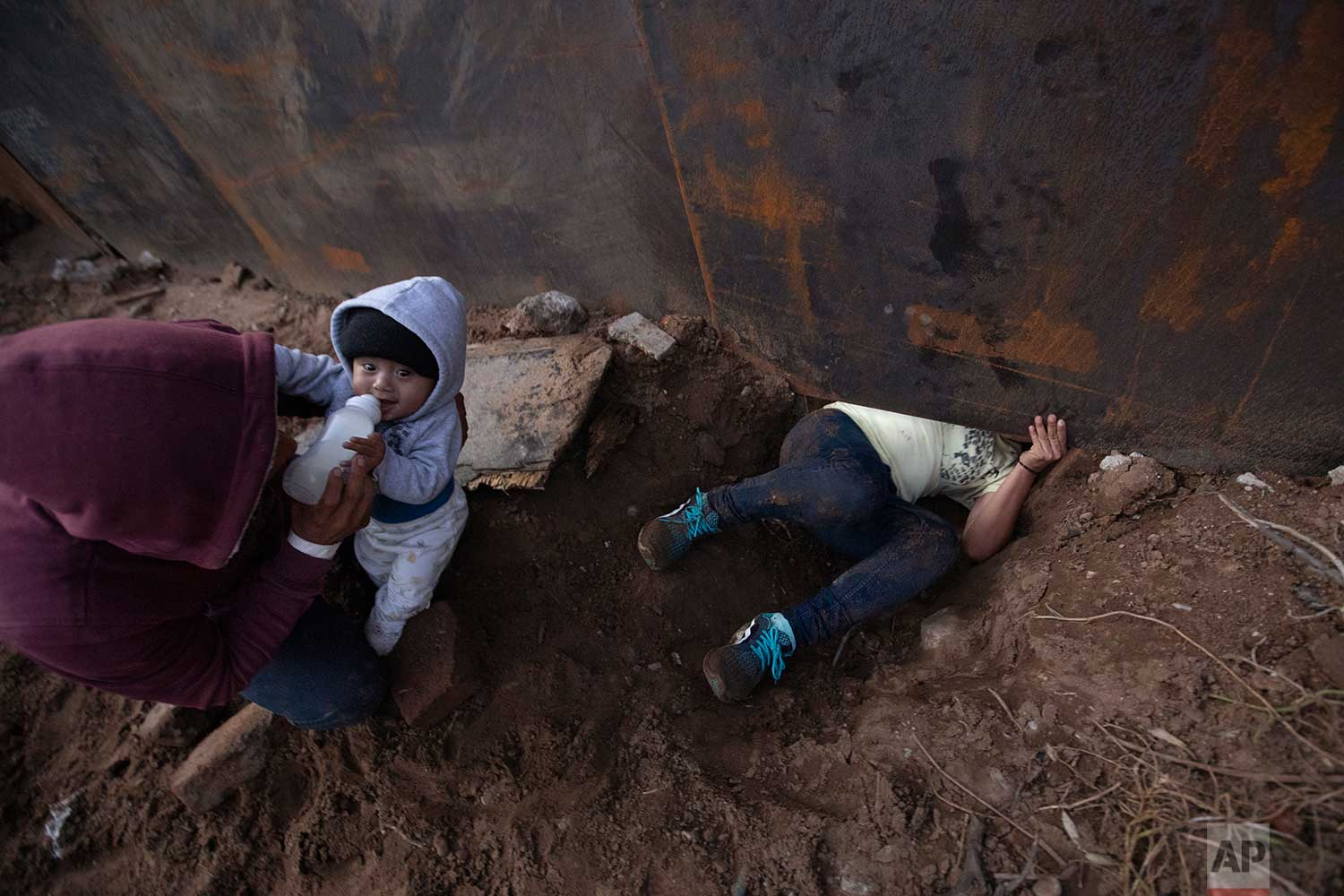 Honduran migrant Joel Mendez, 22, feeds his eight-month-old son Daniel as his partner Yesenia Martinez, 24, crawls through a hole under the U.S. border wall, in Tijuana, Mexico, Friday, Dec. 7, 2018. Moments later Martinez, carrying her son, surrendered to waiting border guards. Mendez stayed behind in Tijuana to work, saying he feared he'd be deported if he crossed. This image won the News Photography Single Shot category in the 2019 Associated Press Media Editors Awards. (AP Photo/Rebecca Blackwell)