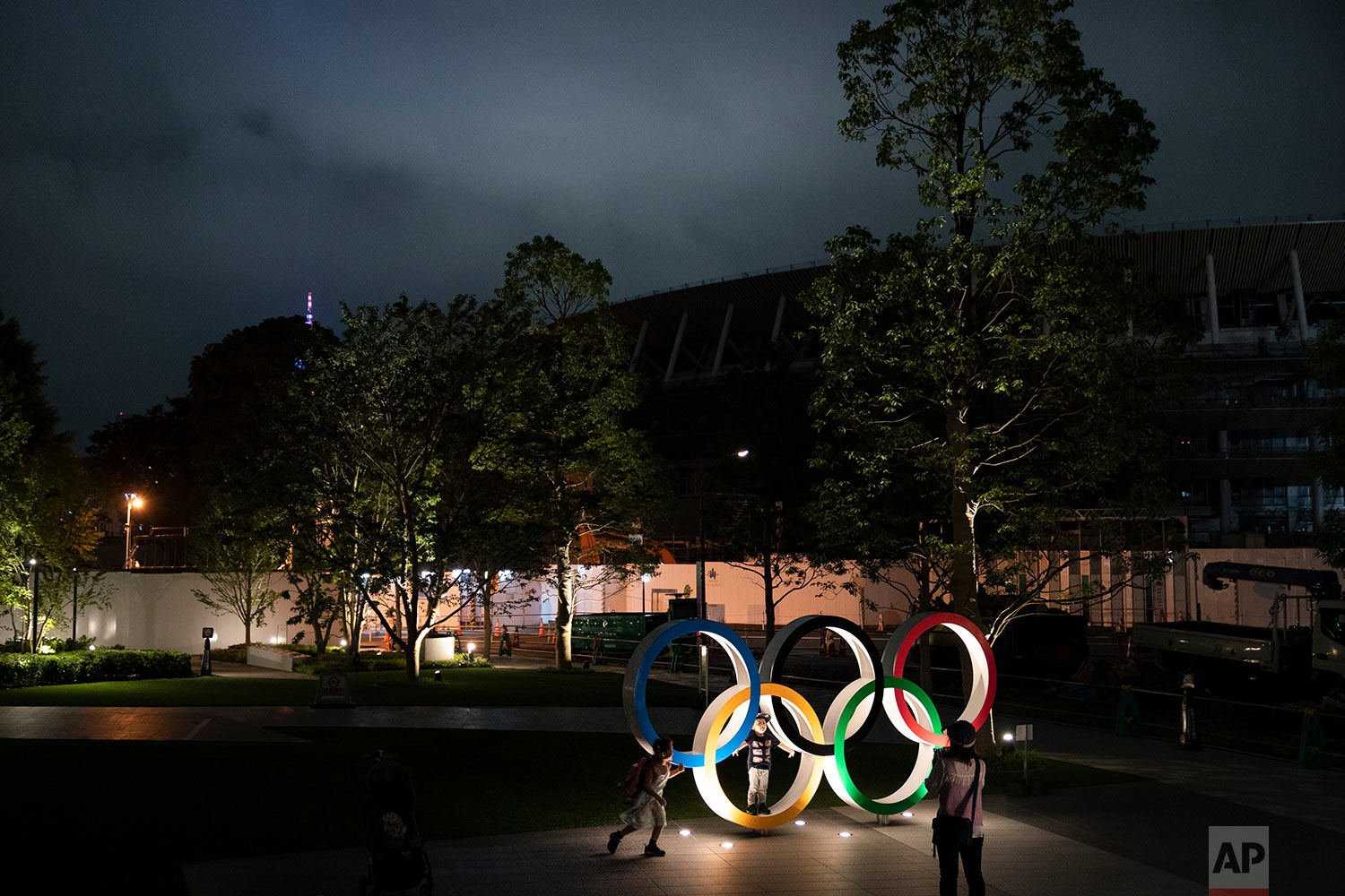 Two children pose for photos with the Olympic Rings in front of New National Stadium in Tokyo, June 23, 2019. (AP Photo/Jae C. Hong)