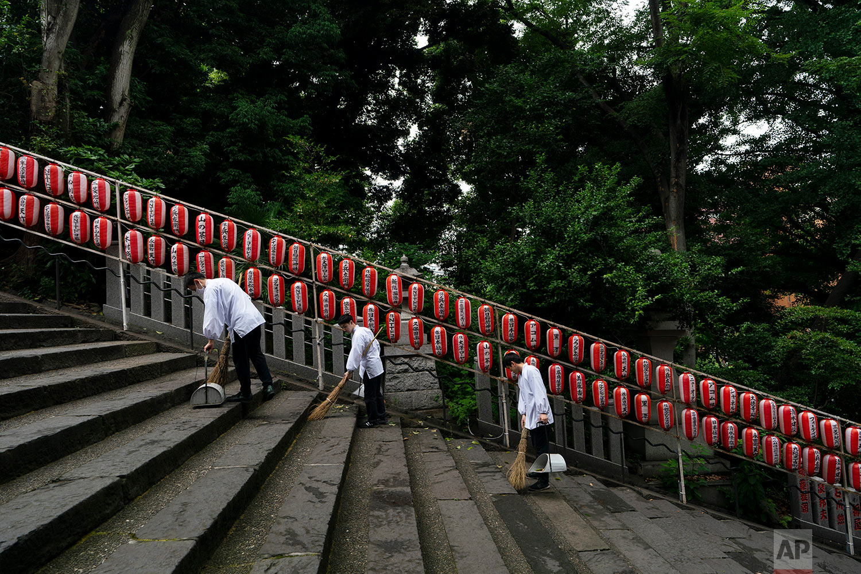 Staff members at the Hie Shrine clean the steps of the shrine in Tokyo, June 8, 2019. (AP Photo/Jae C. Hong)