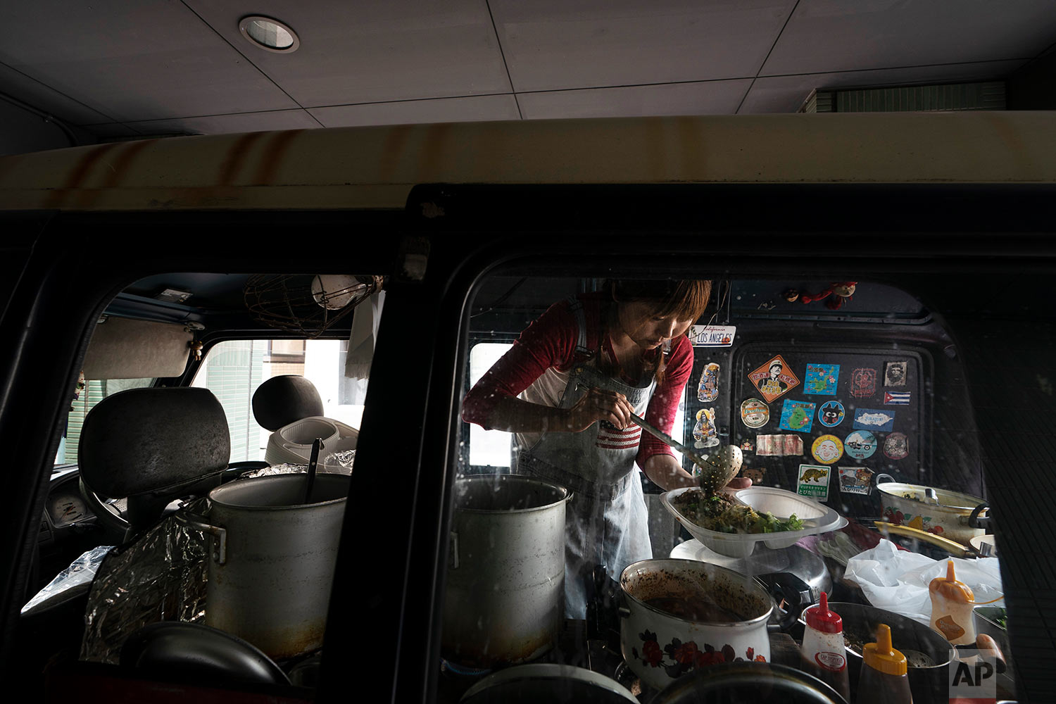 Mijo Nakamura, 38, works in her tiny food truck named Charming Restaurant in the Shibuya district of Tokyo, May 29, 2019. Serving fusion Asian food, Nakamura's food truck only opens for lunch. (AP Photo/Jae C. Hong)
