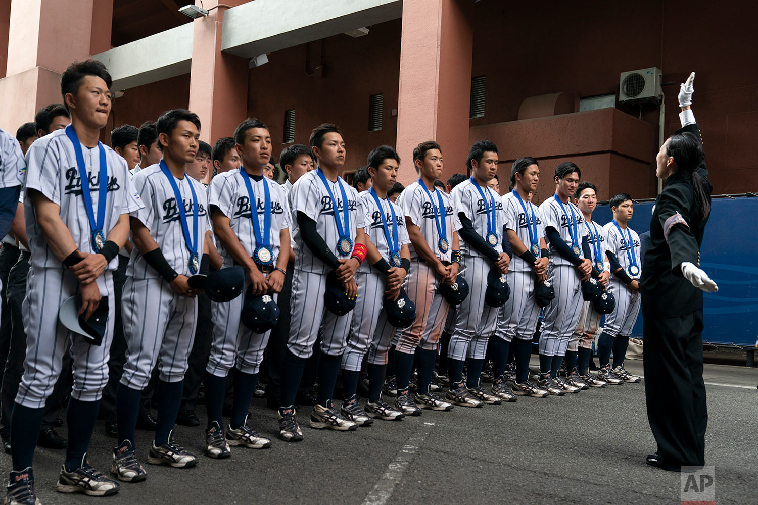 Bukkyo University cheerleading squad leader, Yamaguchi Karin, right, leads the school song in front of the school's baseball players in Tokyo, June 17, 2019, after the team placed second in the 68th All-Japan University Baseball Championship. (AP Photo/Jae C. Hong)