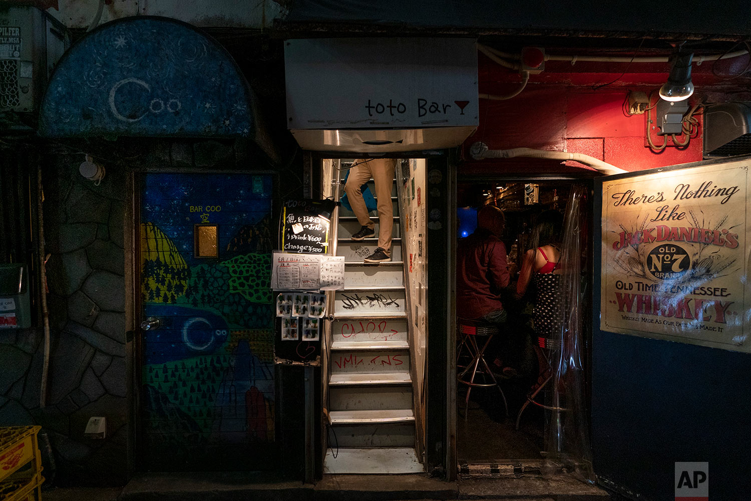 A man pauses briefly while walking down a narrow staircase of a bar in Golden Gai, in Tokyo, June 1, 2019. (AP Photo/Jae C. Hong)