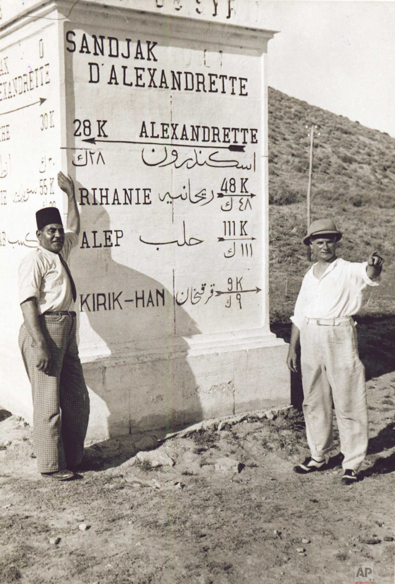Associated Press Foreign Correspondent James A. Mills (1883-1942), right, is pictured with an undentified friend beside a roadside mileage marker near Alexandrette in what is now Turkey, on September 2, 1938. At the time, Mills was reporting from the Middle East.