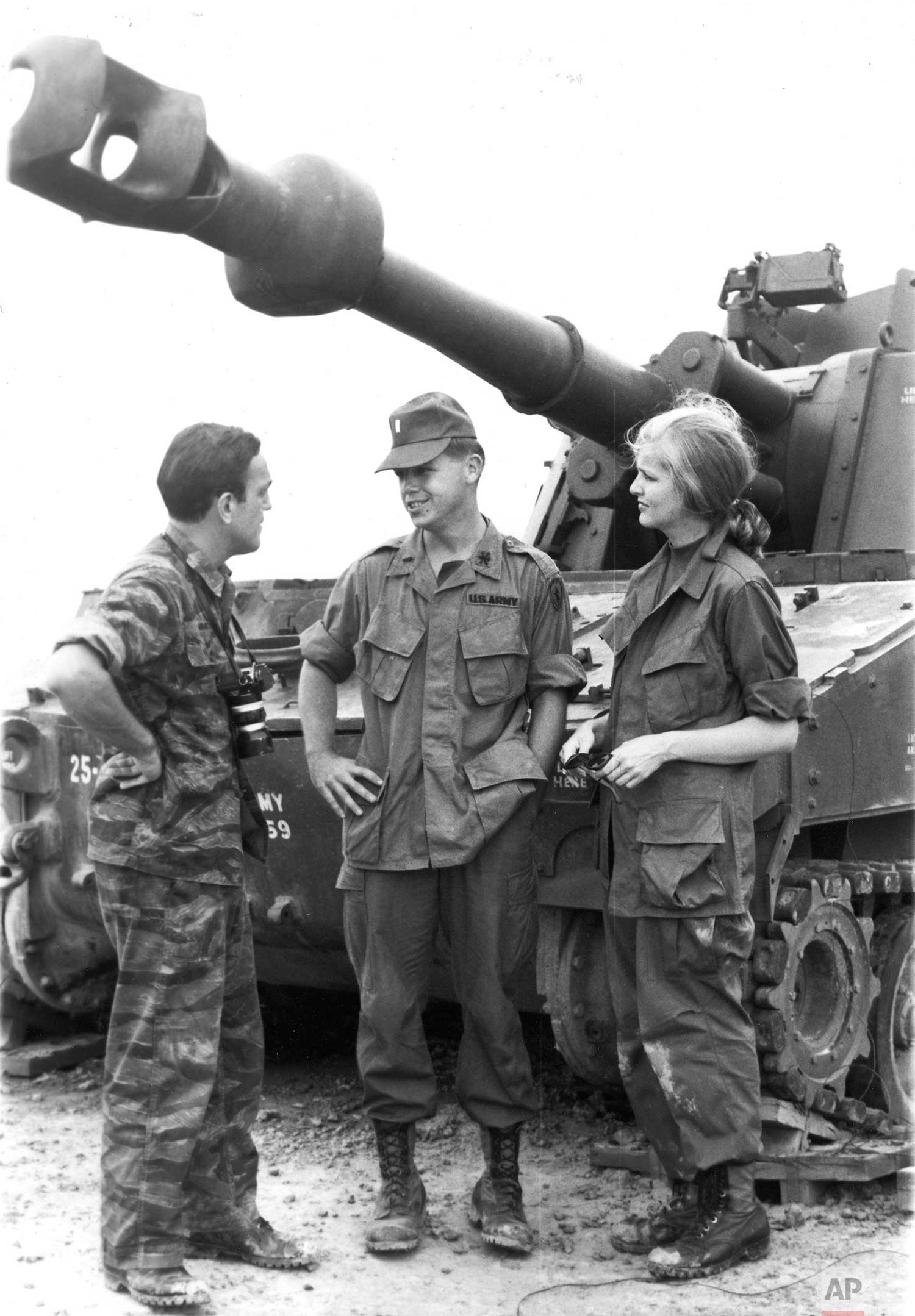 AP newsmen Peter Arnett, left, and Mary Ann (Kelly) Smith discuss armored operations with a tankman beneath the muzzle of a heavy tank of the 25th Infantry Division at Cu Chi, Vietnam (Sept. 1967). (AP Photo)