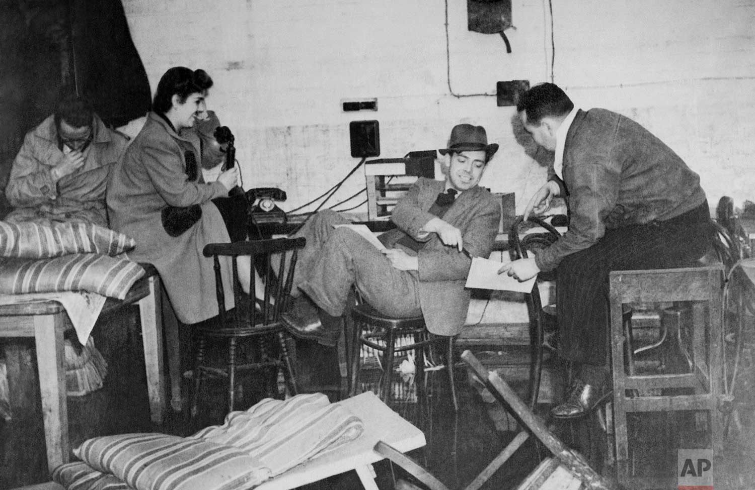 Members of the London staff of the Associated Press went ahead with their work, sending news to the world from temporary quarters in the flooded basement of The Associated Press building on Sept. 25, 1940 after a German bomb landed outside the front door. From left are: G.H.P. Anderson, Anne Keefe, Edwin Stout and Drew Middleton. (AP Photo)