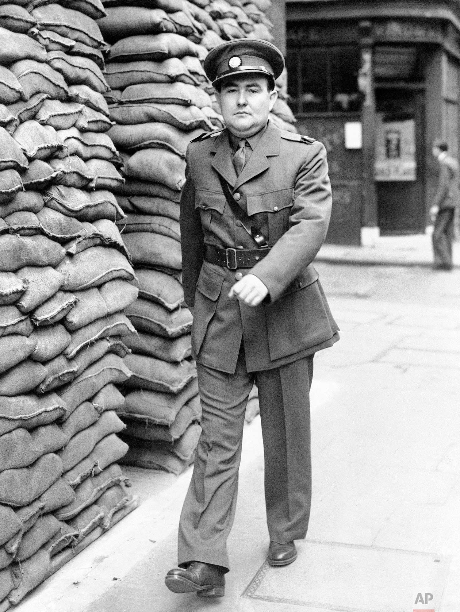 """Drew Middleton, Associated Press reporter in London, has become a war correspondent and is to going to France next week, October 9-10th. He will wear the uniform of correspondents with the British Army: an officers uniform with special badges and a """"Press"""" armlet. Drew Middleton, Associated Press correspondent is shown in his uniform passing the sandbagged Associated Press building in London on Oct. 24, 1939. (AP Photo)"""